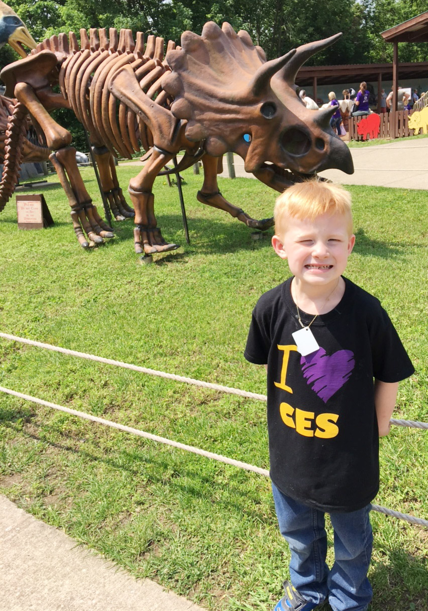 CES kindergartener Jayden Maupin poses in front of a dinosaur.