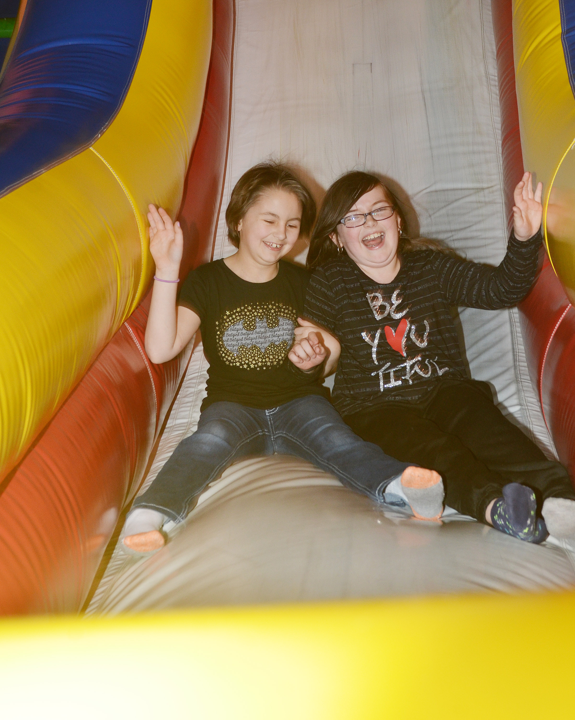 CES fourth-graders Raenna Jefferson, at left, and Lauren Pace slide down an inflatable.