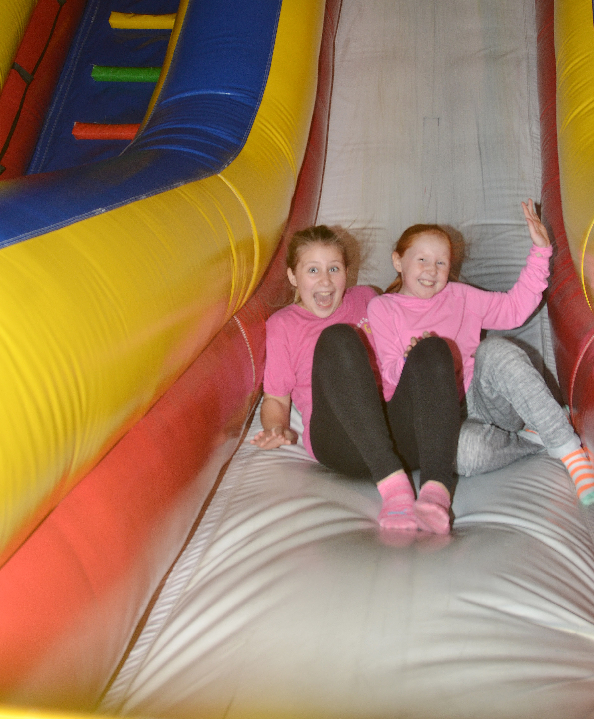CES fourth-graders Addysen Dotson, at left, and Nora Harris slide down an inflatable.