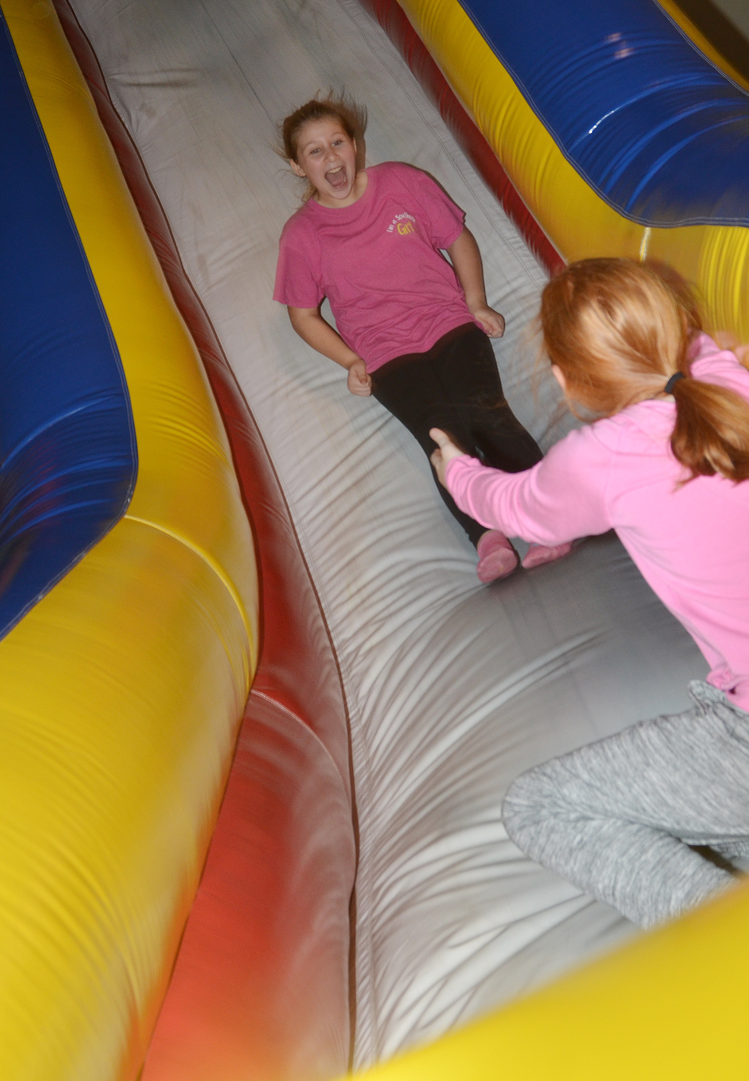 CES fourth-grader Addysen Dotson slides down an inflatable to classmate Nora Harris.