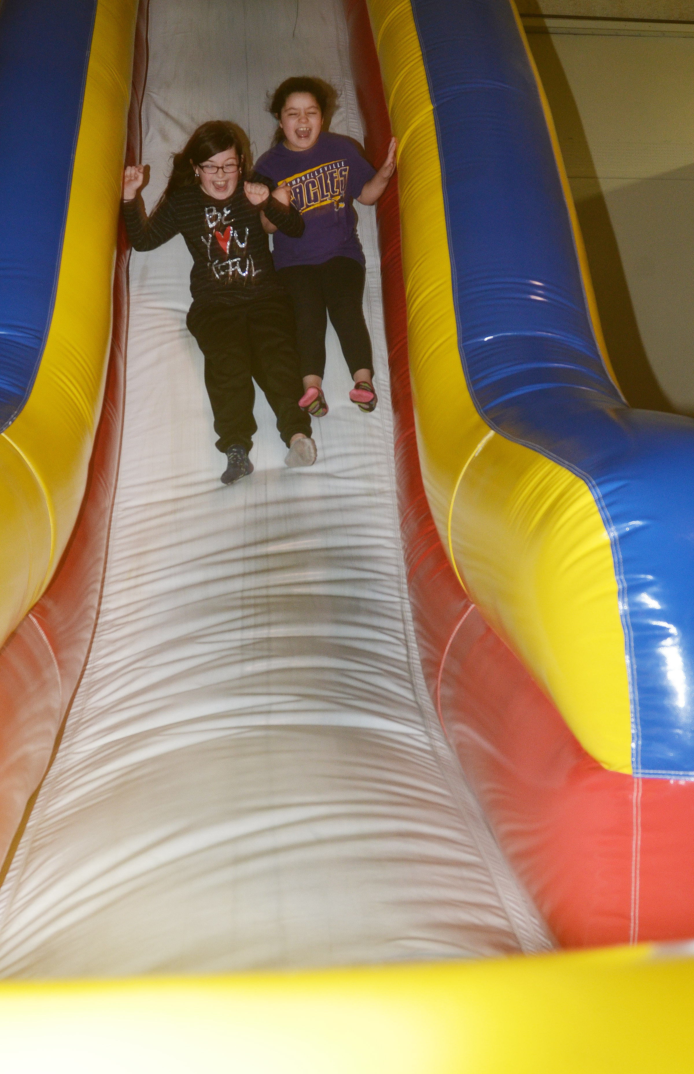 CES fourth-graders Lauren Pace, at left, and Brooklyn Boudreaux slide down an inflatable.
