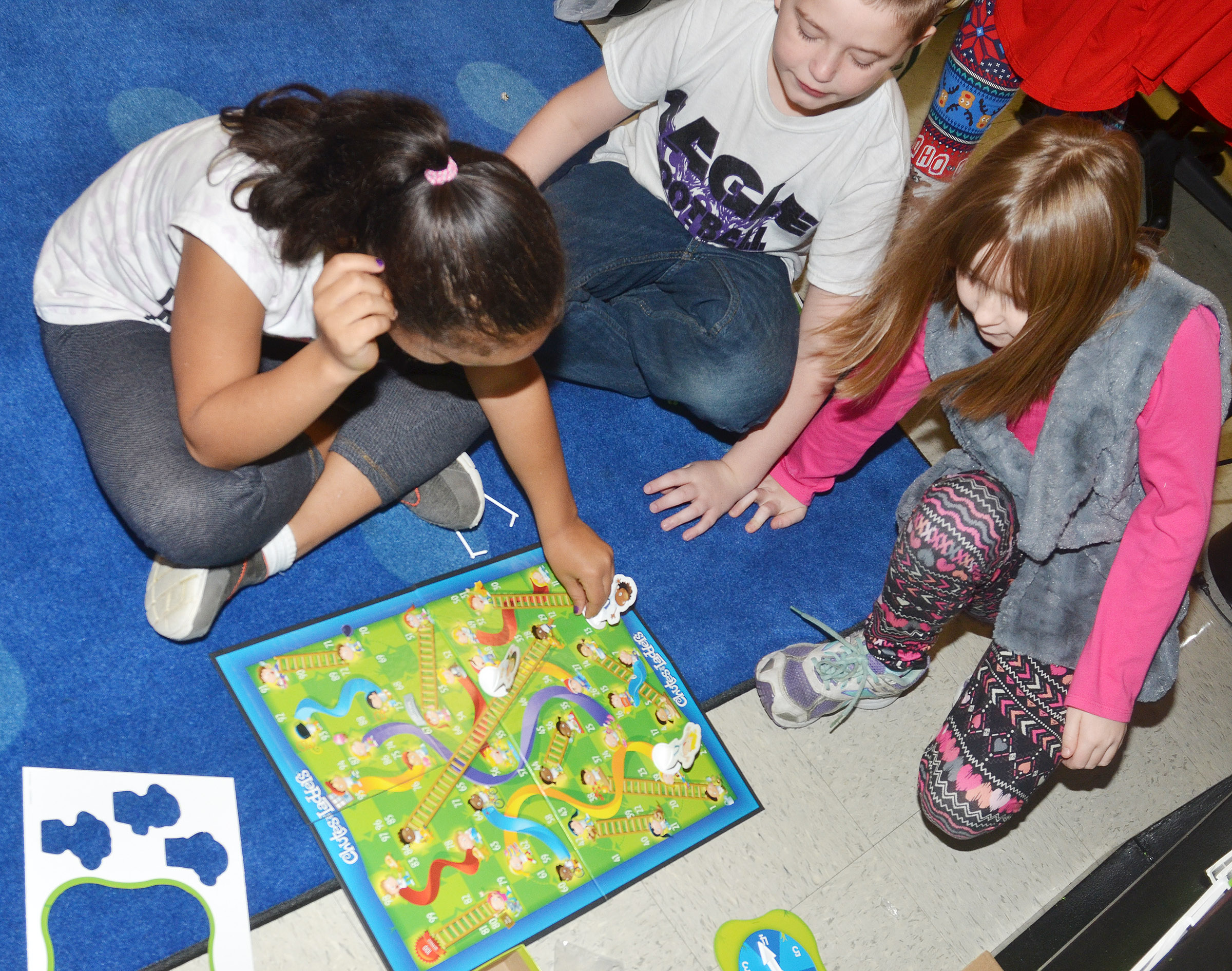 CES second-graders play Chutes and Ladders. From left are Amani Bridgewater, Kevin Bradfield and Gracie Murphy.
