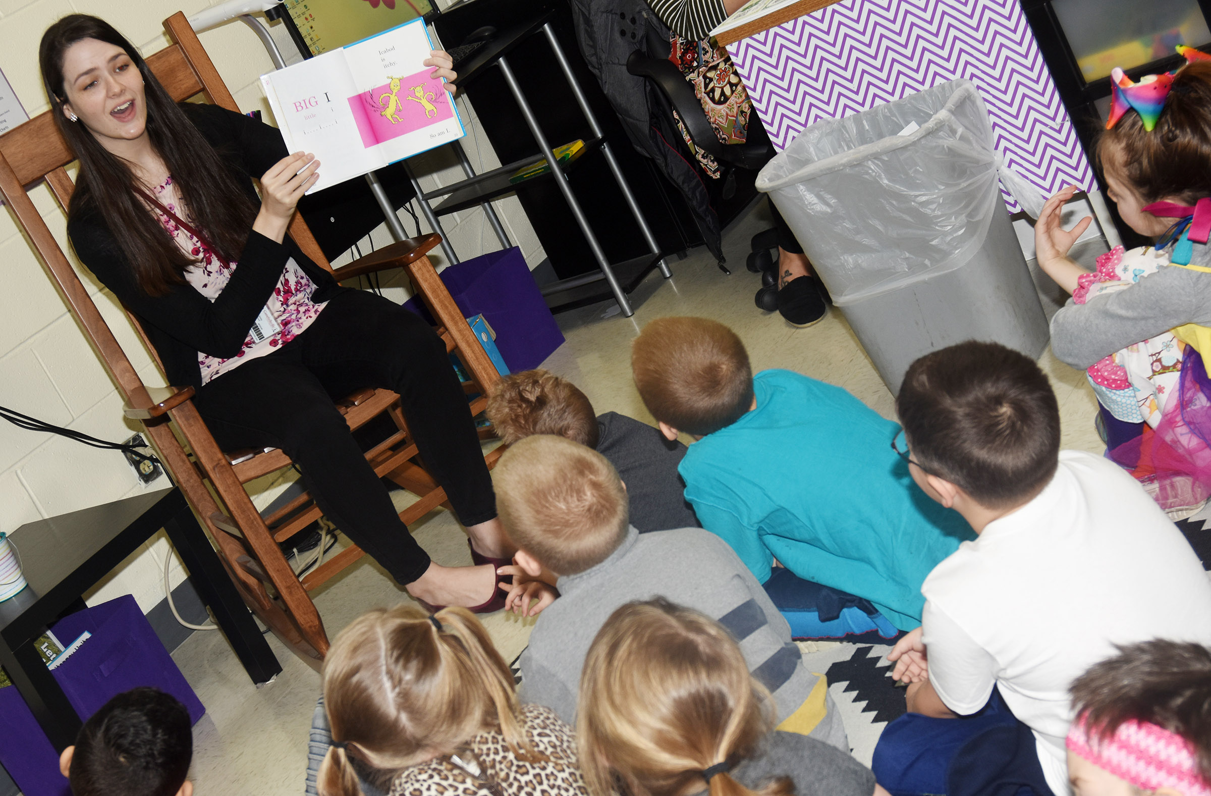CU education student Emily Ford reads a Dr. Seuss book to CES first-grade students.