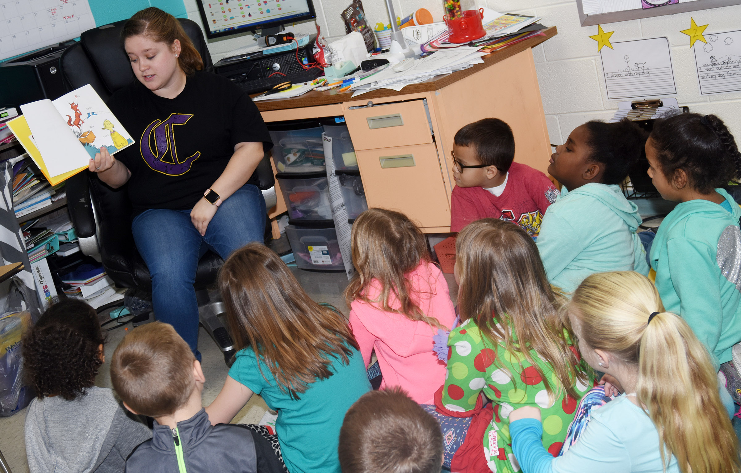 CU education student Jordyn Bray reads a Dr. Seuss book to CES first-grade students.