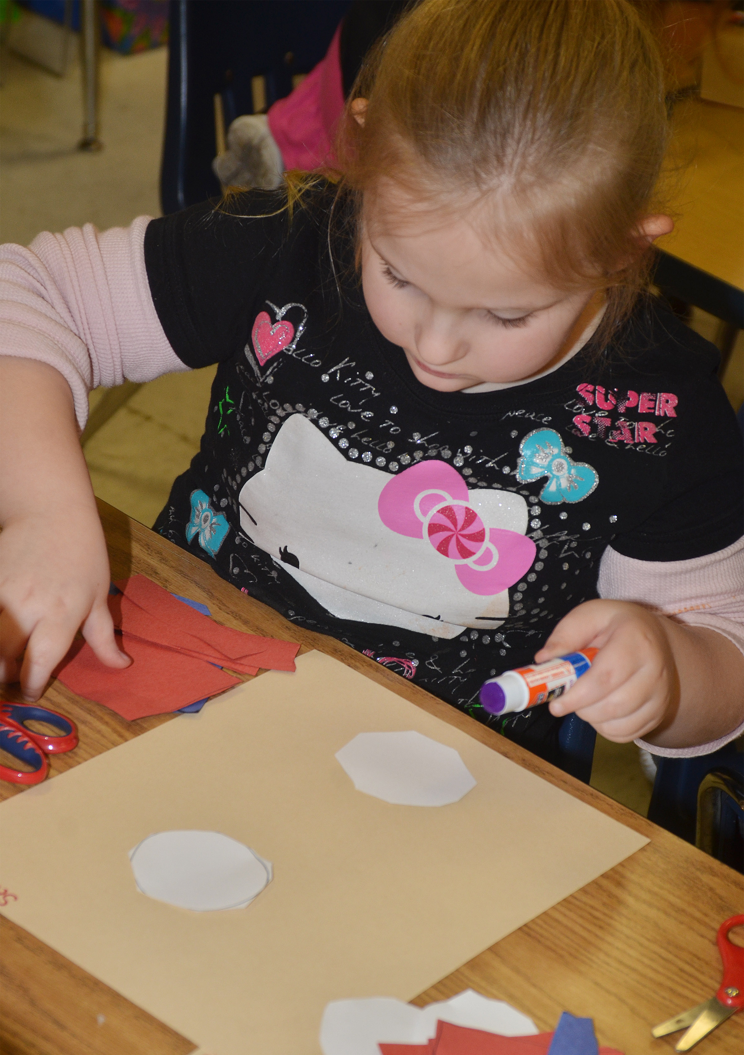 CES kindergartener Scarlett Cook glues the pieces of her Thing 1 character to her construction paper.