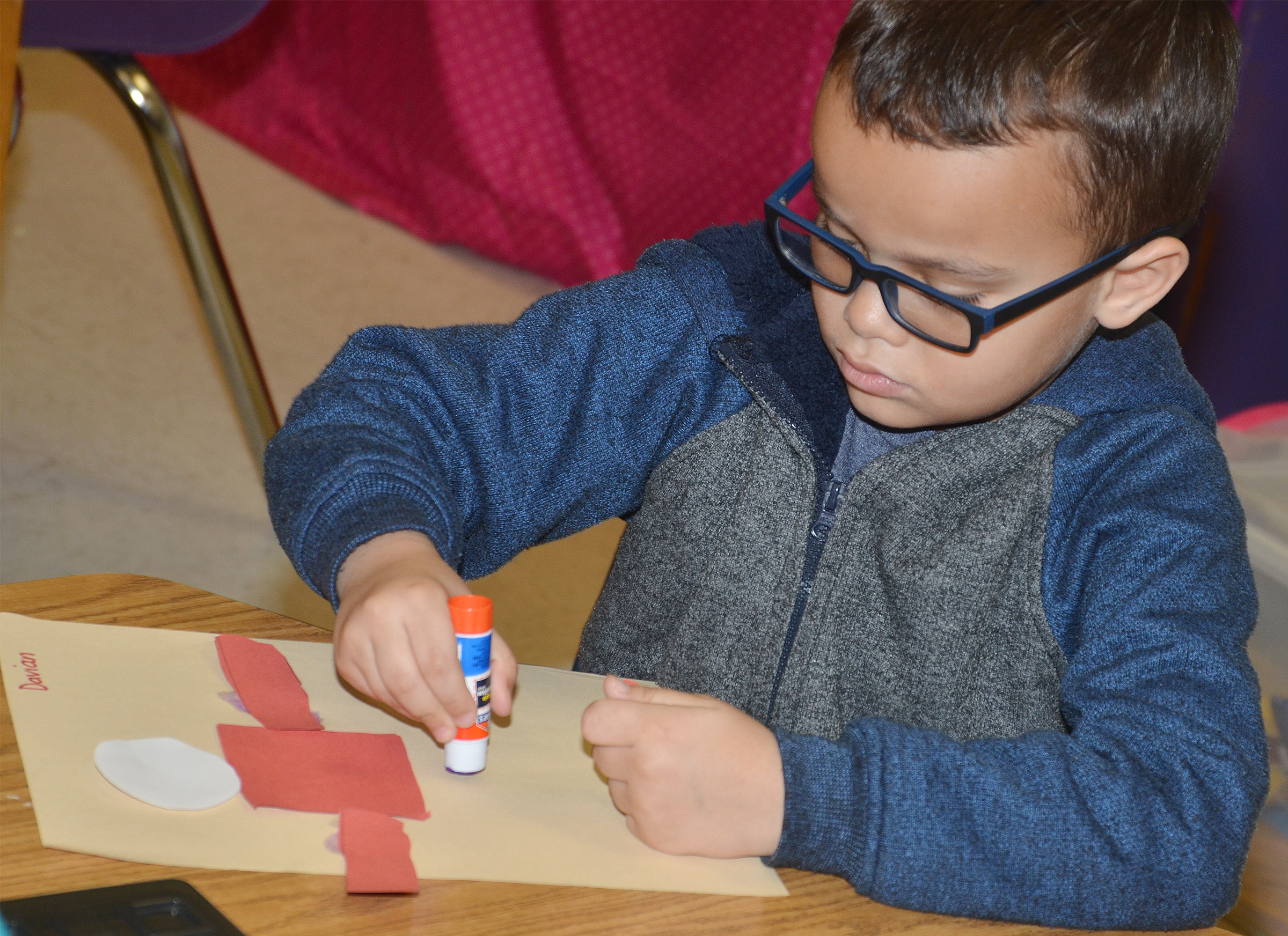 CES kindergartener Davian Taylor glues the pieces of his Thing 1 character to his construction paper.