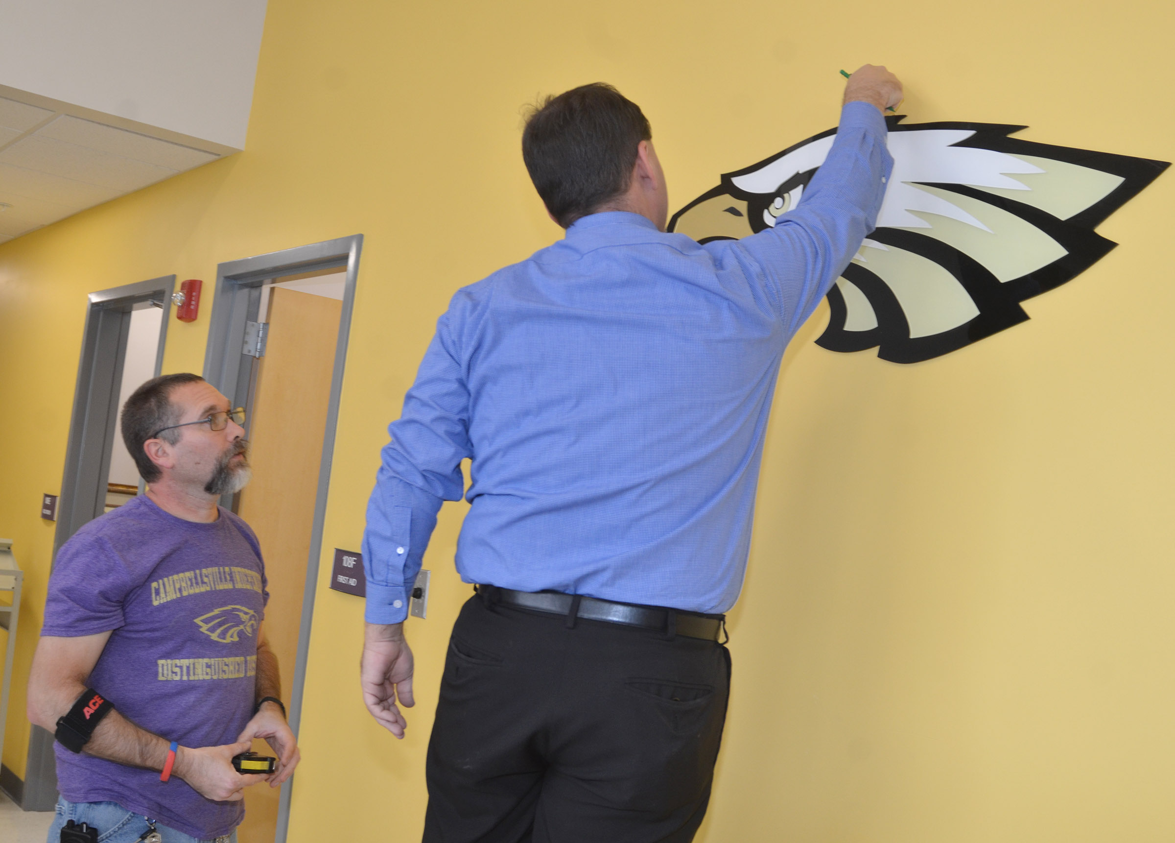 CES maintenance worker Randy Bricken Jr., at left, and Principal Ricky Hunt install the CES letters and eagle.