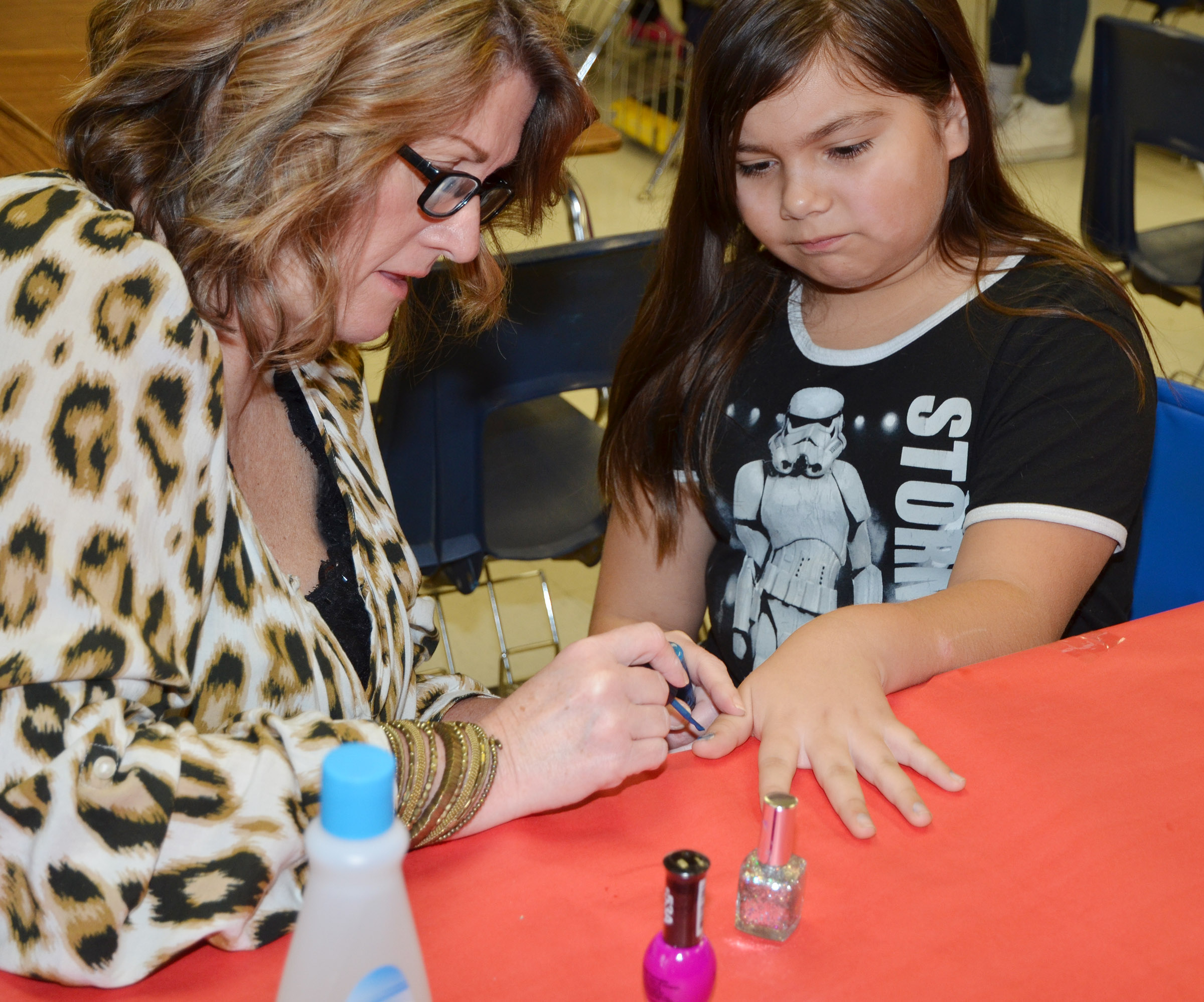 CMS teacher Donna White paints fifth-grader Aaliyah Nunez's nails.