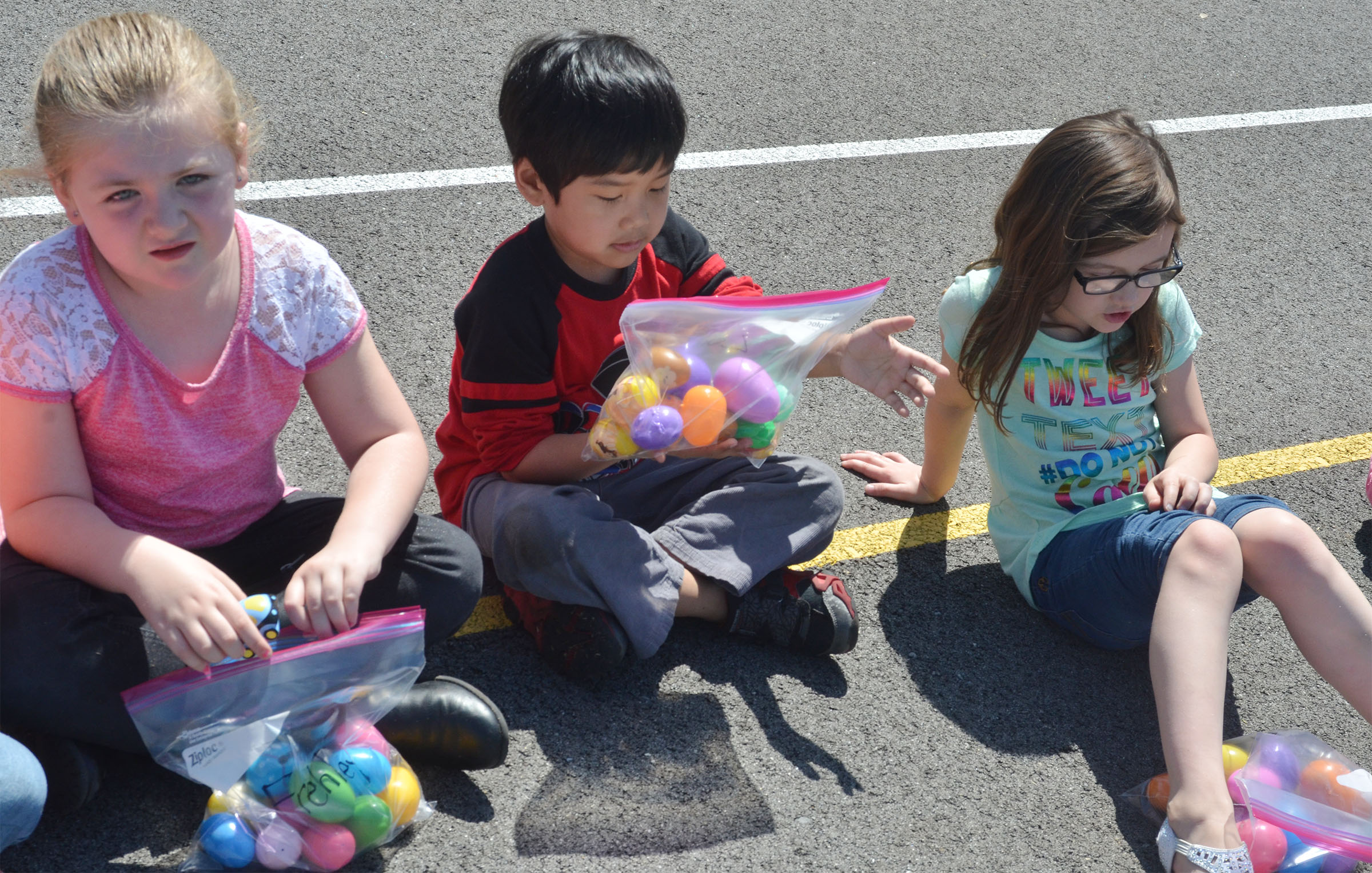 From left, CES first-graders Frehley Whitlow, Zach Hak and Anna Keith look to see what's inside their Easter eggs.