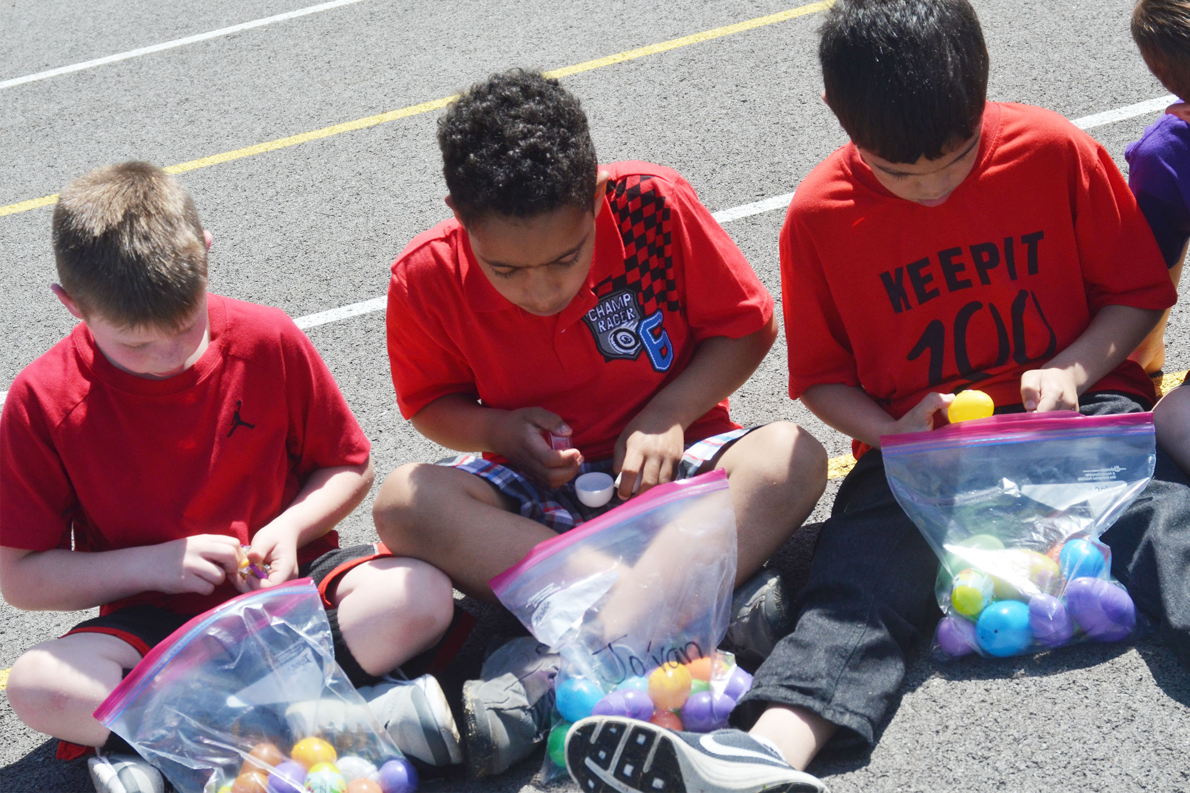 From left, CES first-graders Brody Sidebottom, Jo'van Goins and Xadrian Fugate look inside their Easter eggs.