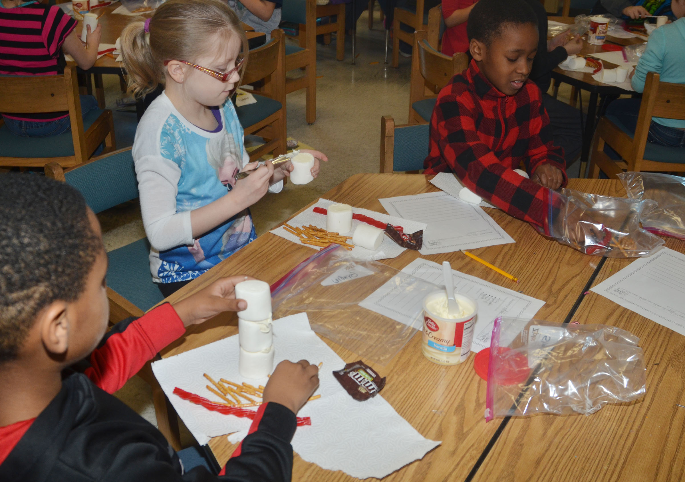 CES third-graders, from left, Shaiden Calhoun, Gracie Pendleton and John Gholston make their edible snowmen.