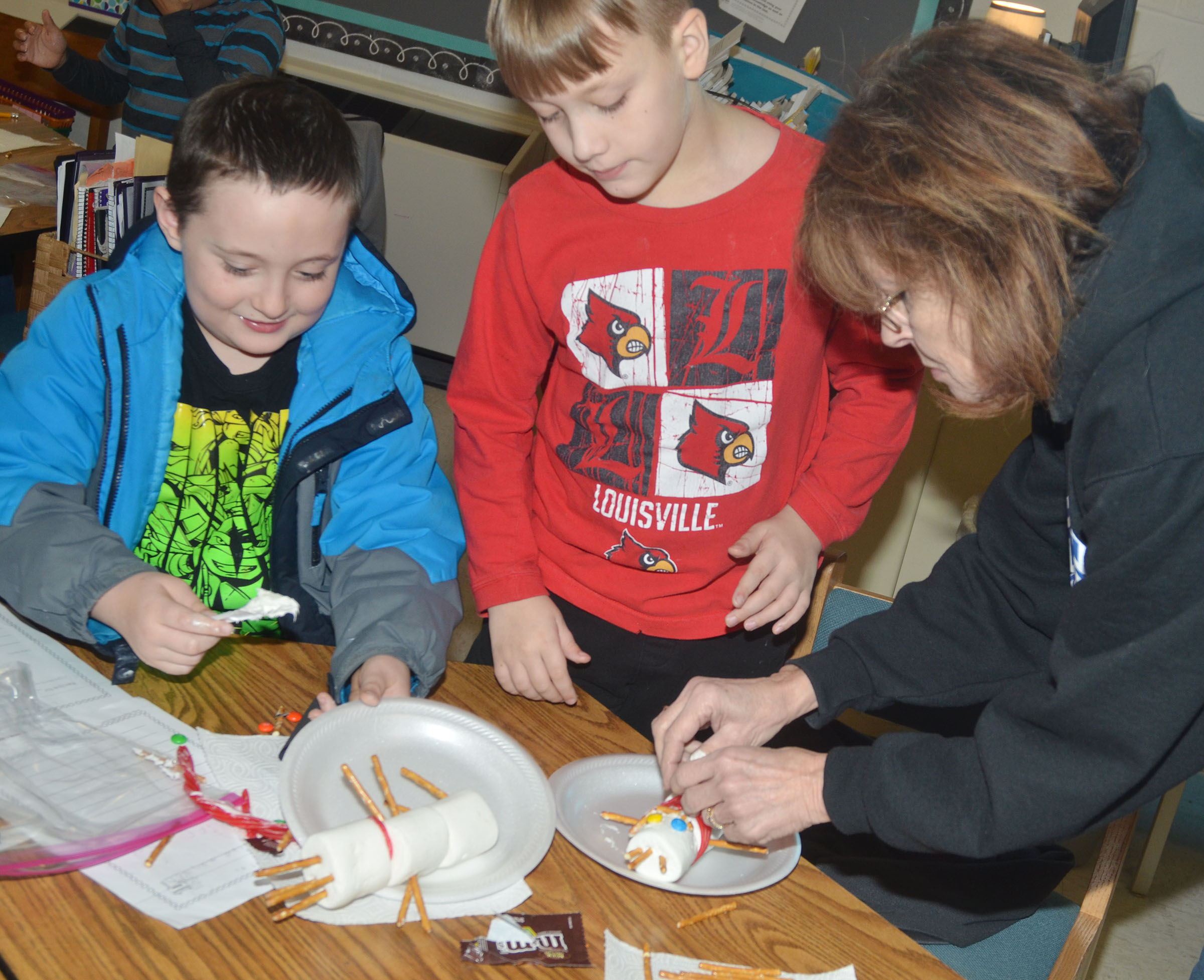 CES third-grade teacher Marcia Sharp helps Izak Burress build his edible snowman.