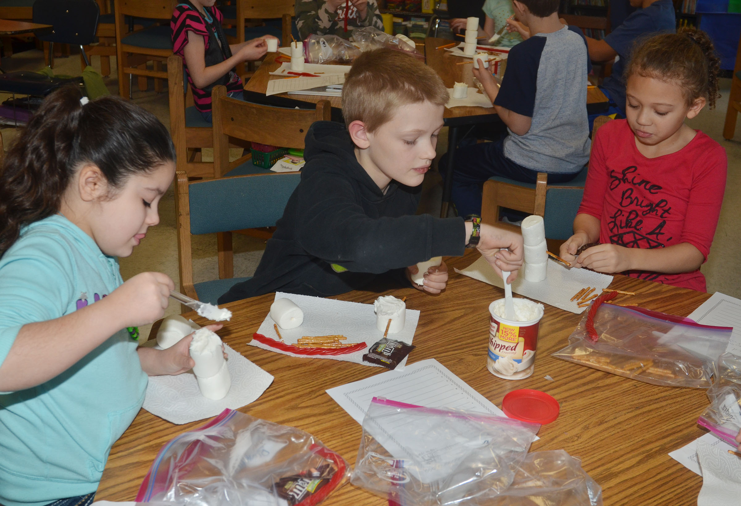 From left, CES third-graders Brooklyn Boudreaux, Jonathan Releford and Alicia Spaulding make their edible snowmen.