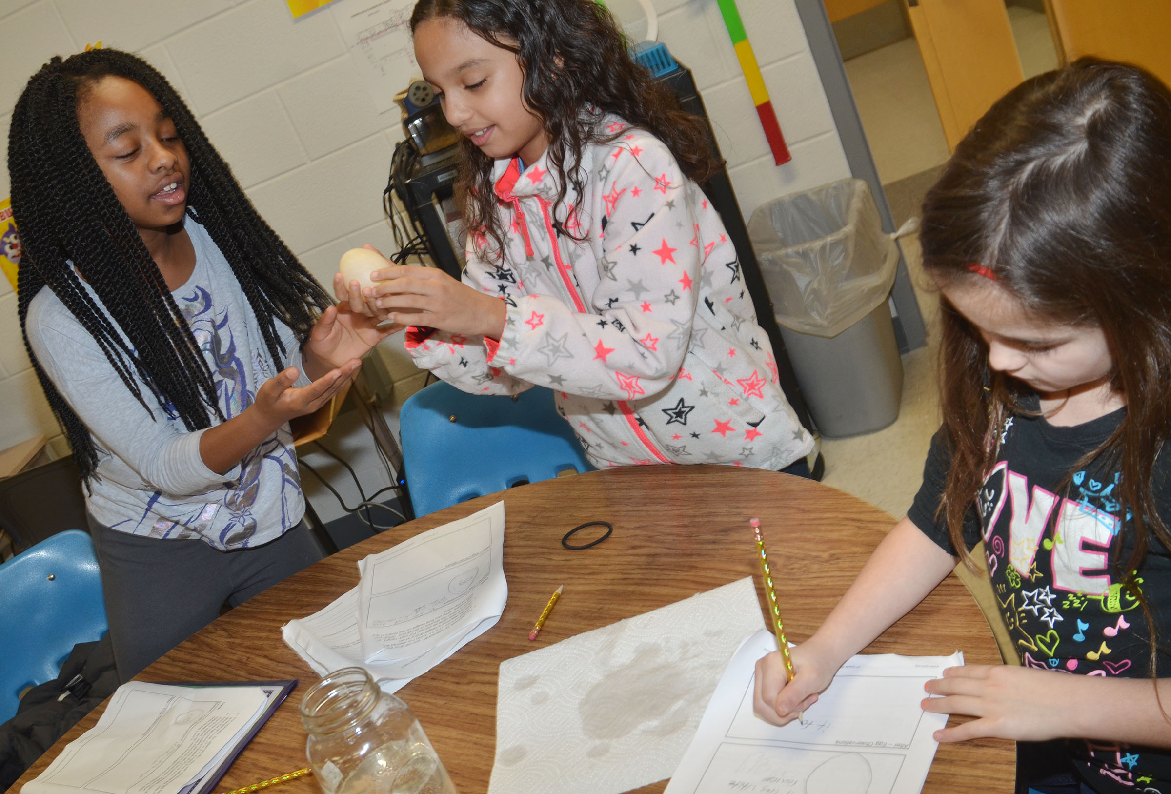 CES third-graders Tiffani Gaddie, at left, and Alyssa Knezevic, center, feel their egg after it has been soaking in vinegar for three days as Alexis Wolford, at right, records their observations.