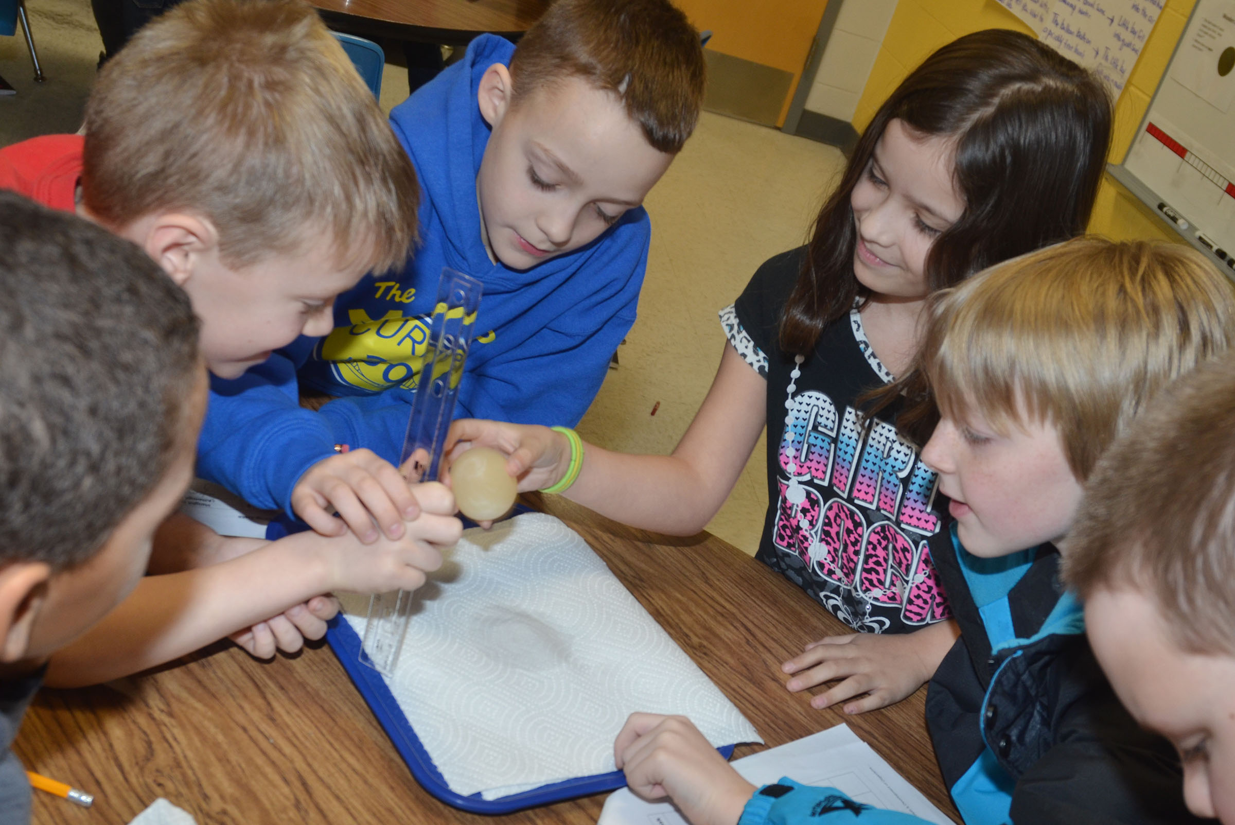 CES third-grader Alexis Wolford drops an egg to see if its membrane will protect it from breaking, as her classmates watch.