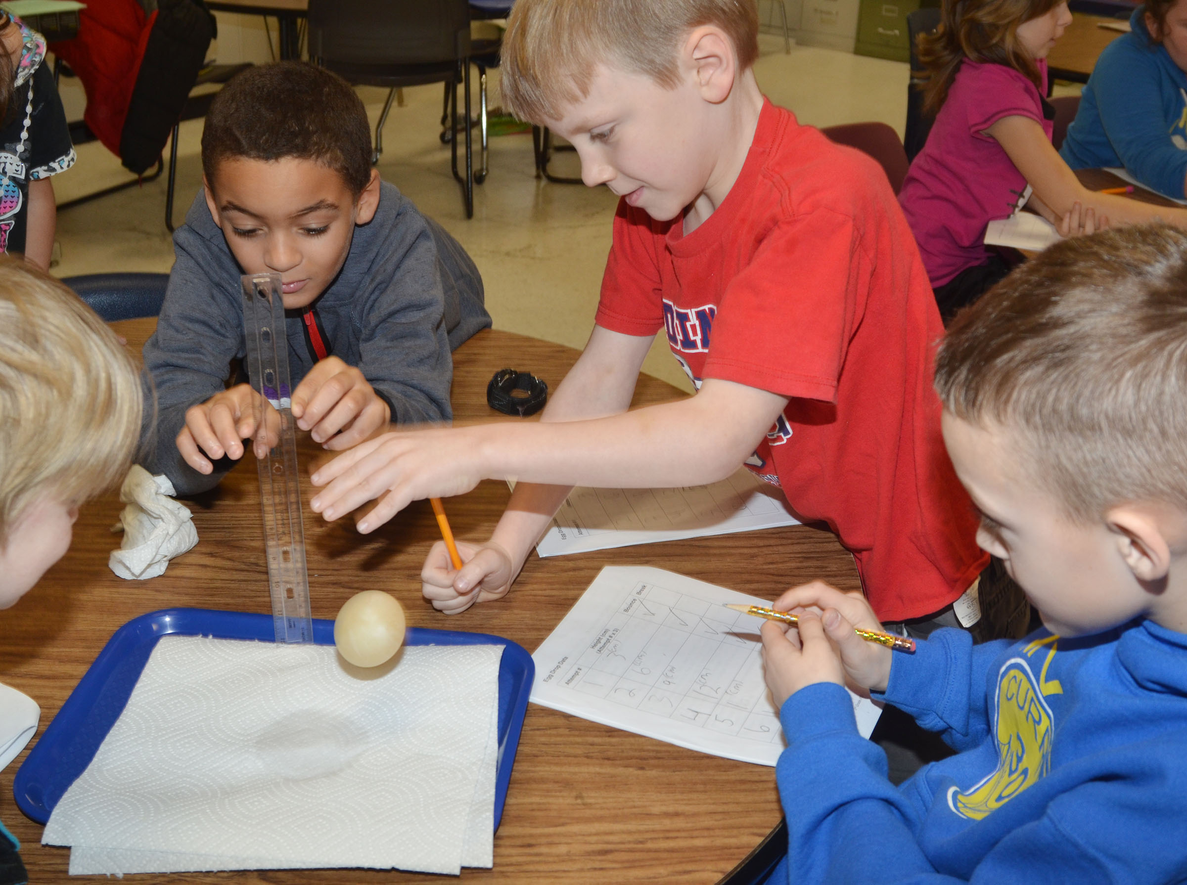 CES third-graders, from left, Jaden Barbee, Connor Coots and Caysen Tungate watch as their egg is dropped to see if its membrane will protect it from breaking.