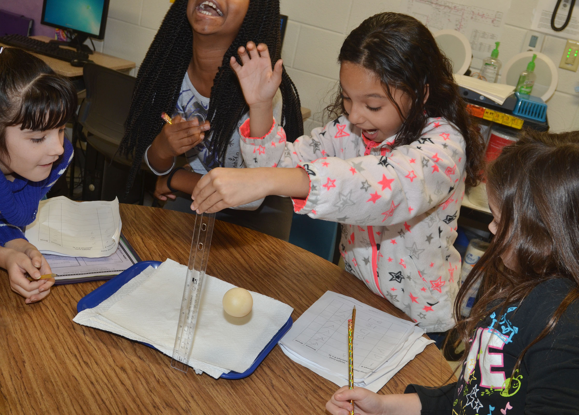 CES third-grader Alyssa Knezevic drops her egg to see if it will break.