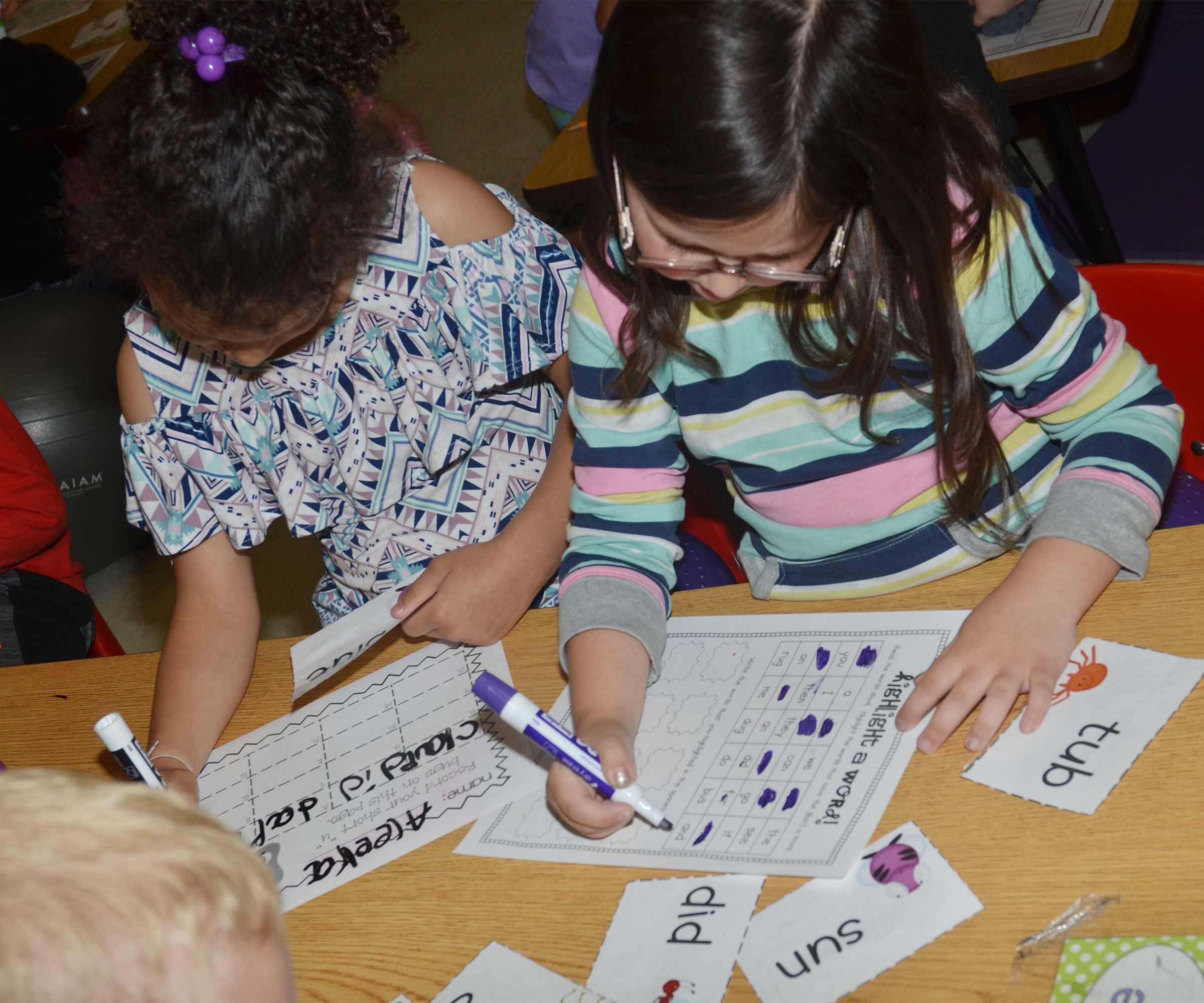 "CES kindergarteners Aleeya Spaulding, at left, and Trinity Clark highlight words that have the short ""u"" sound."