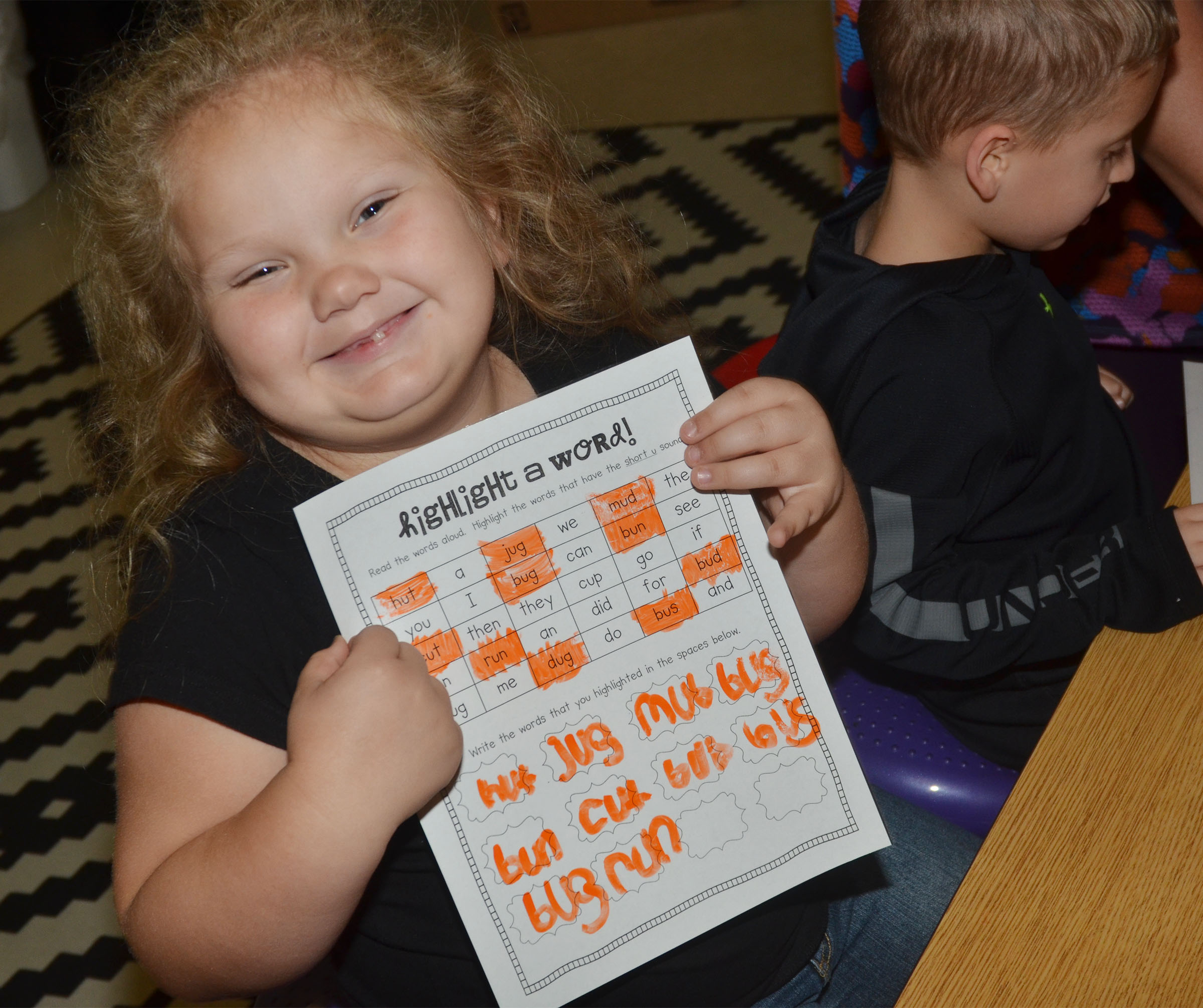 "CES kindergartener ReAnna Jeffries holds her worksheet in which she highlighted all the words that have the short ""u"" sound."