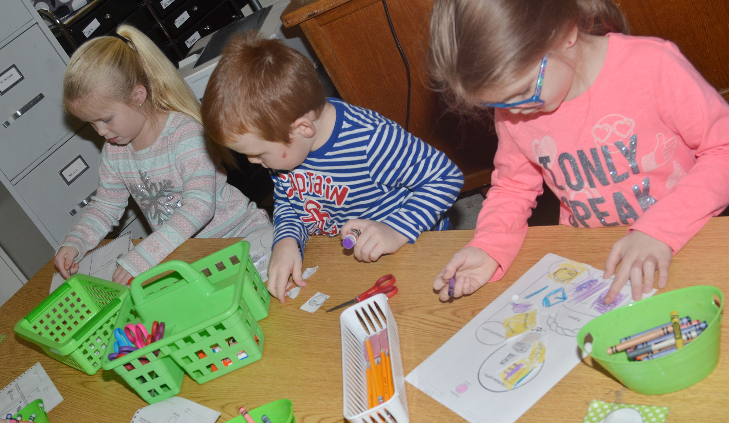 From left, CES kindergarteners Lillie Judd, Daven Davis and Zoe Weddle color their worksheets and cut out their pictures.