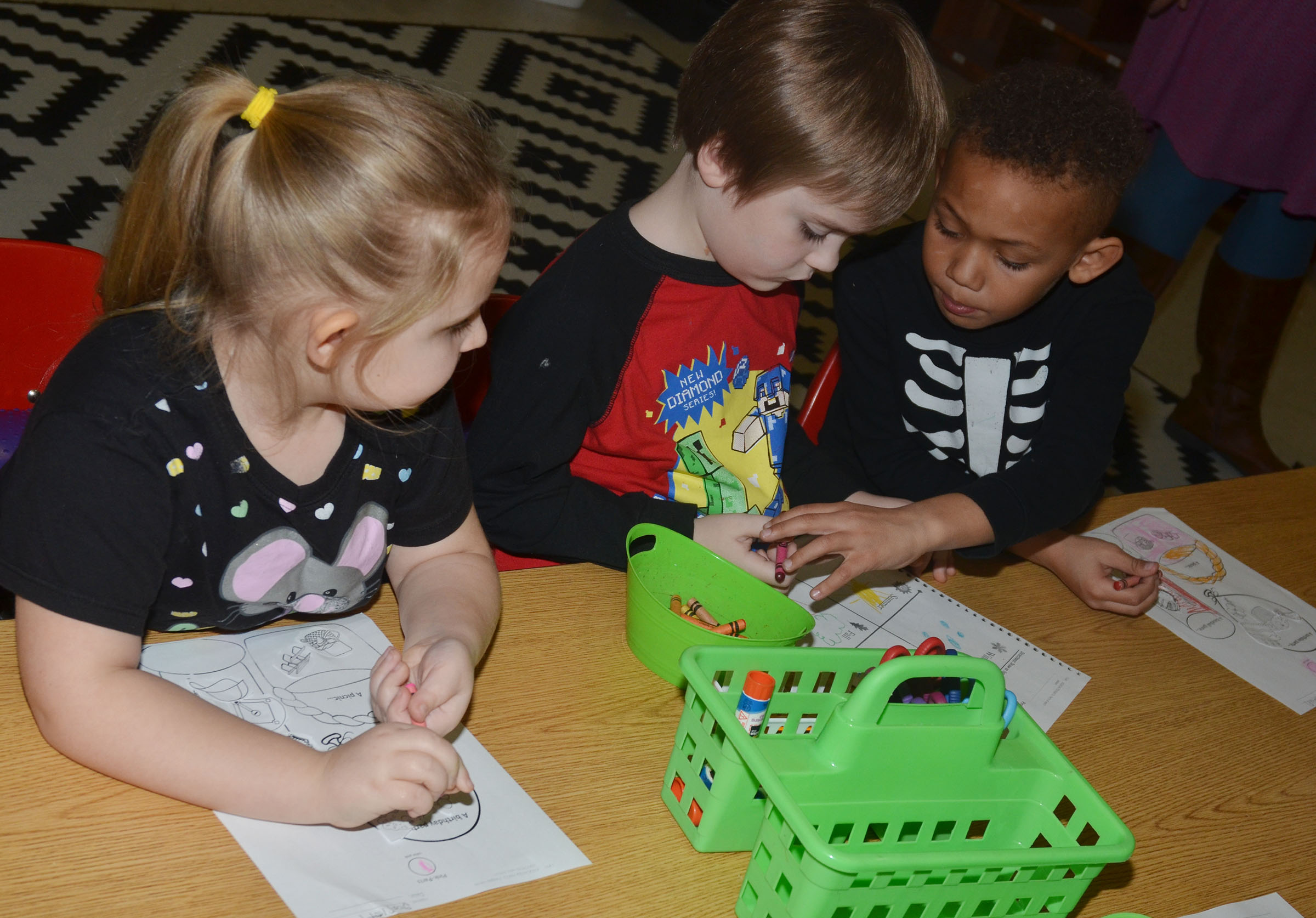 CES kindergarteners, from left, Laurna McKenzie, Gavin Williams and Treshaun Robinson color their worksheets.