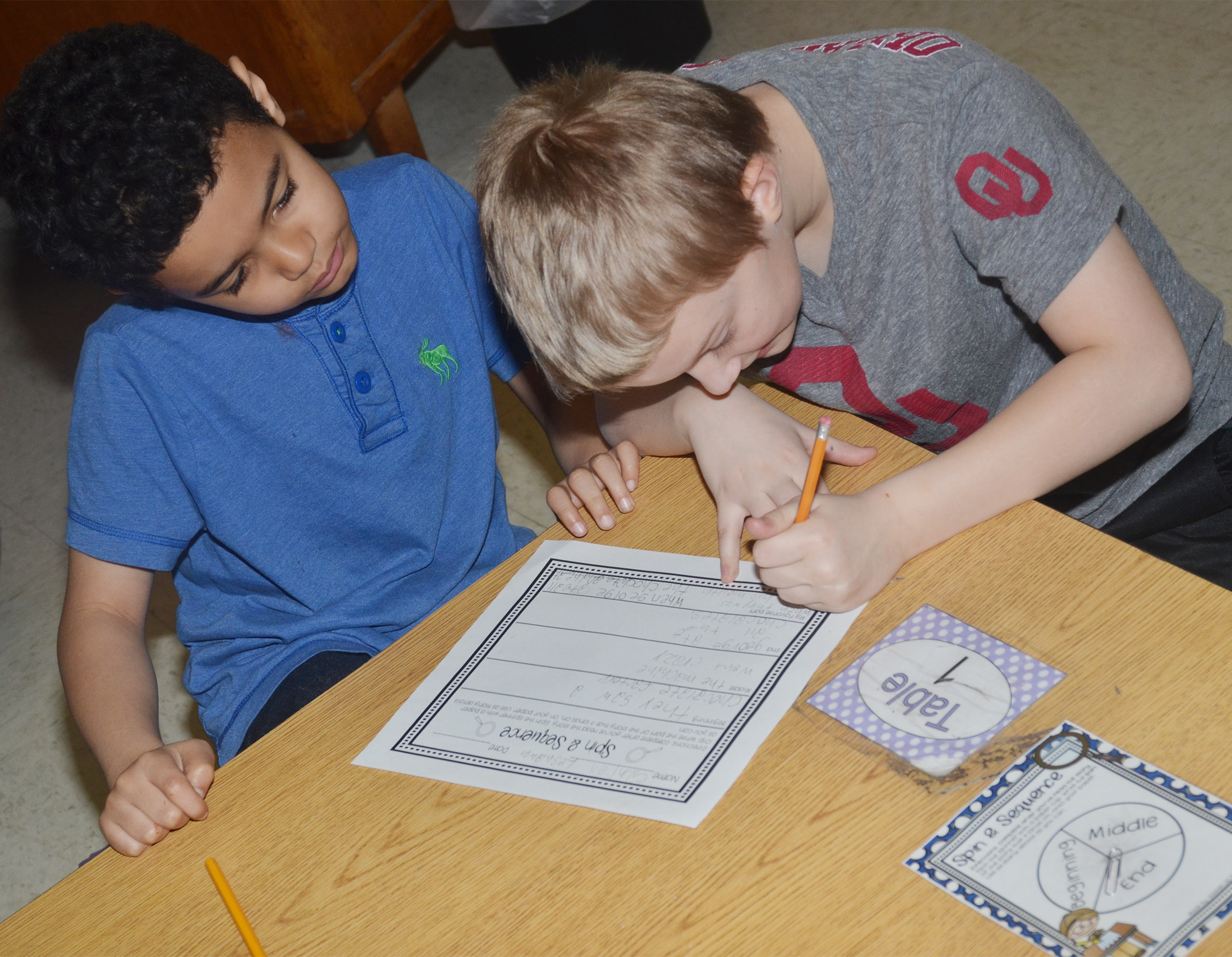 "CES second-graders Leshawn Hamilton, at left, and Camren Skaggs write about their favorite part of ""Curious George Goes to the Chocolate Factory."""