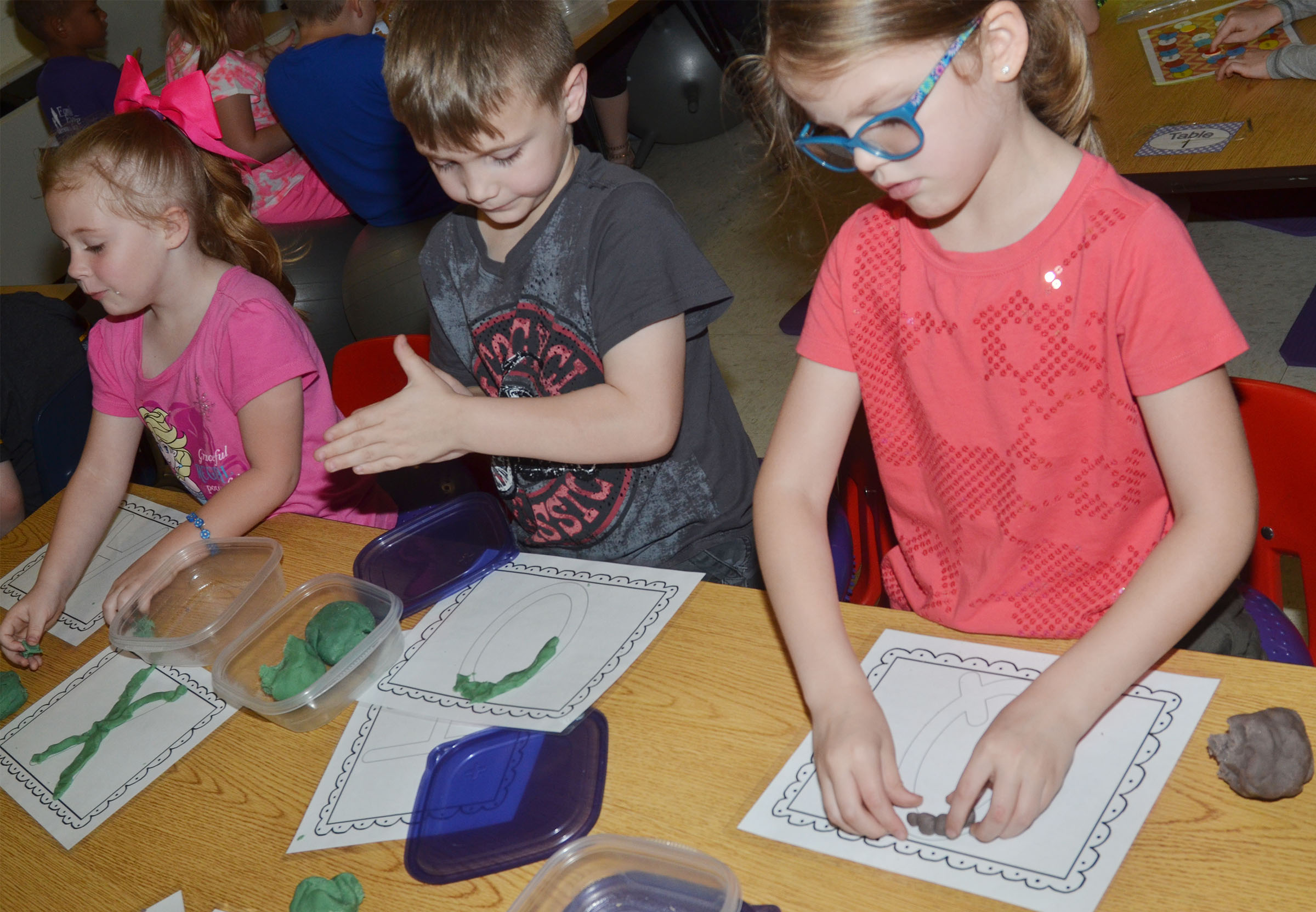 CES kindergartener Zoe Weddle and her friends make letters out of Play-Doh.