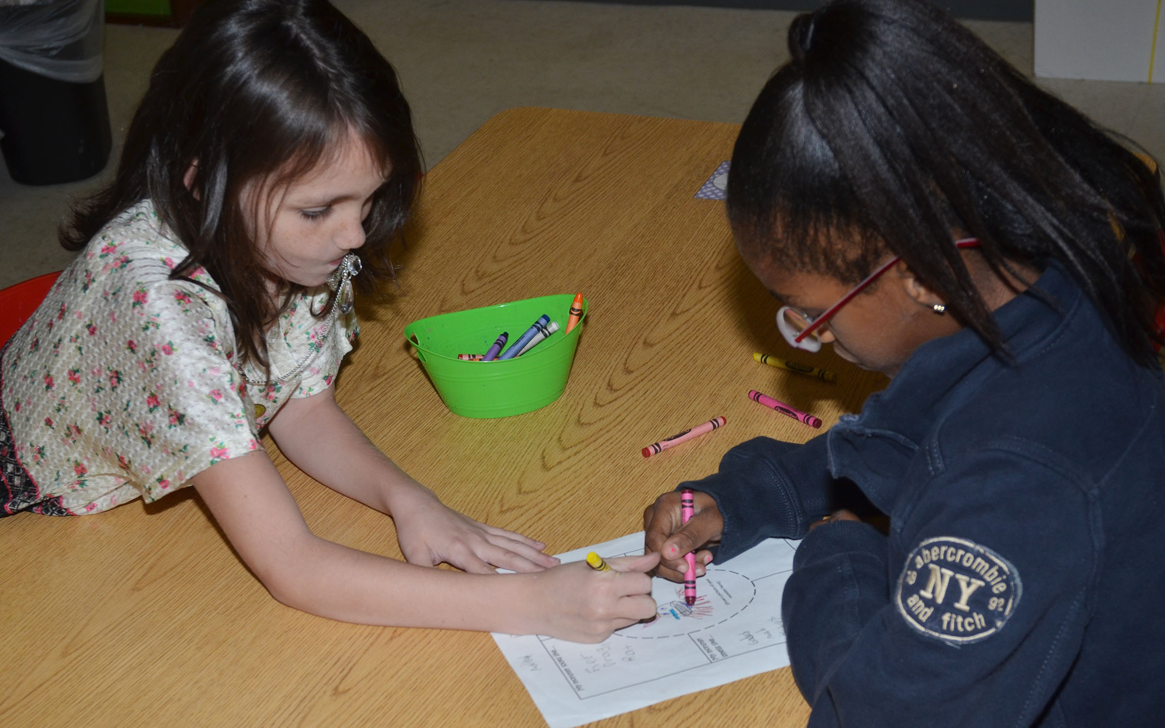 CES third-graders Paige Ritchie, at left, and Maliyah Harris put finishing touches on the drawing of their monster.