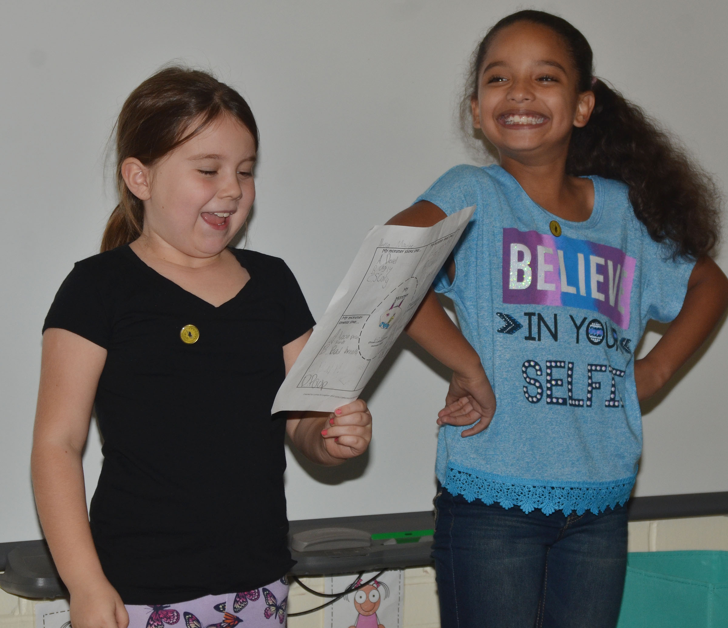 CES third-graders Maylee Wilds, at left, and Aleecia Knezevic tell their classmates about their monster.