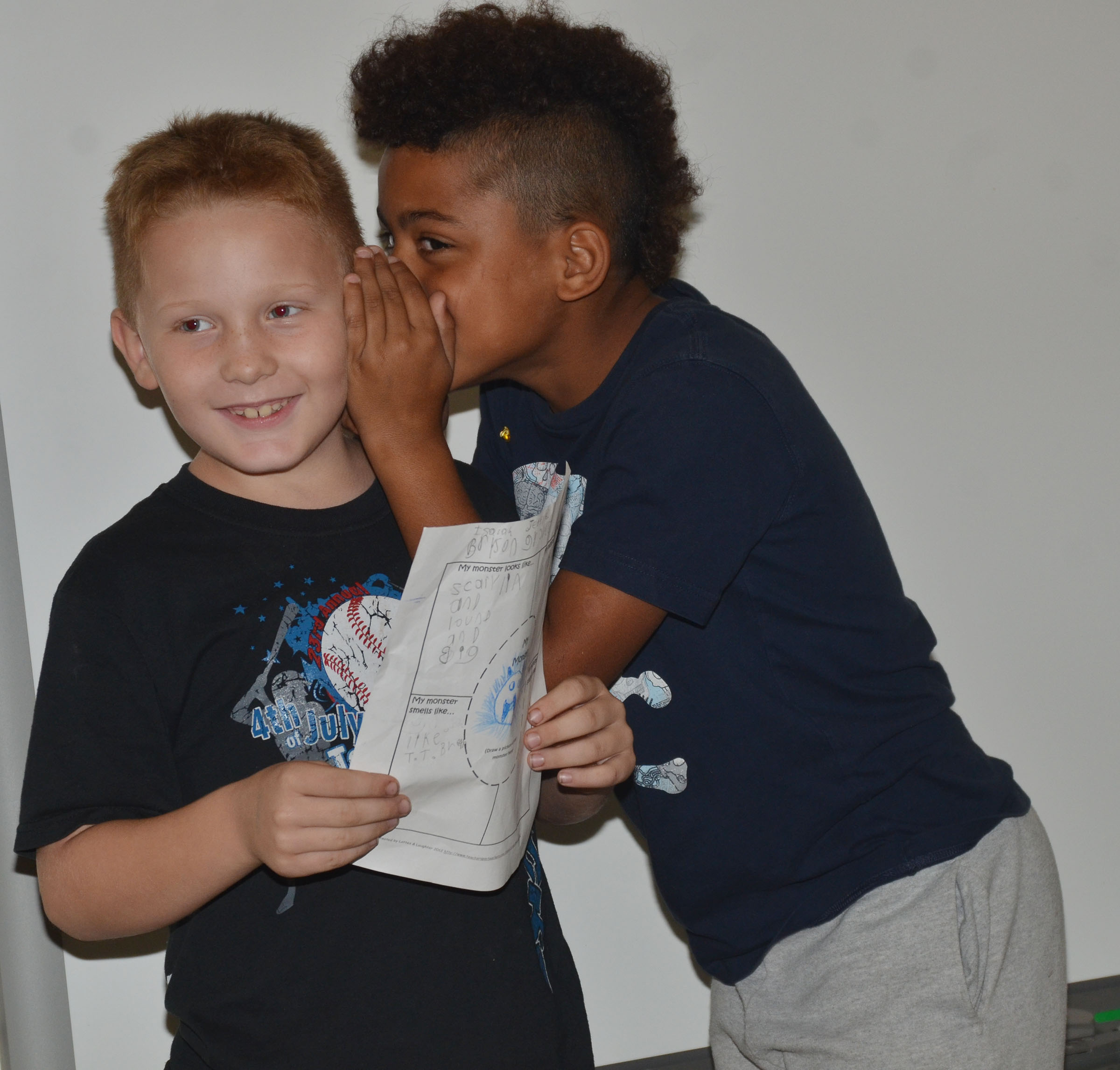 CES third-grader Bryson Groves whispers something to Isaiah Jeffries about their monster so they can tell their classmates.