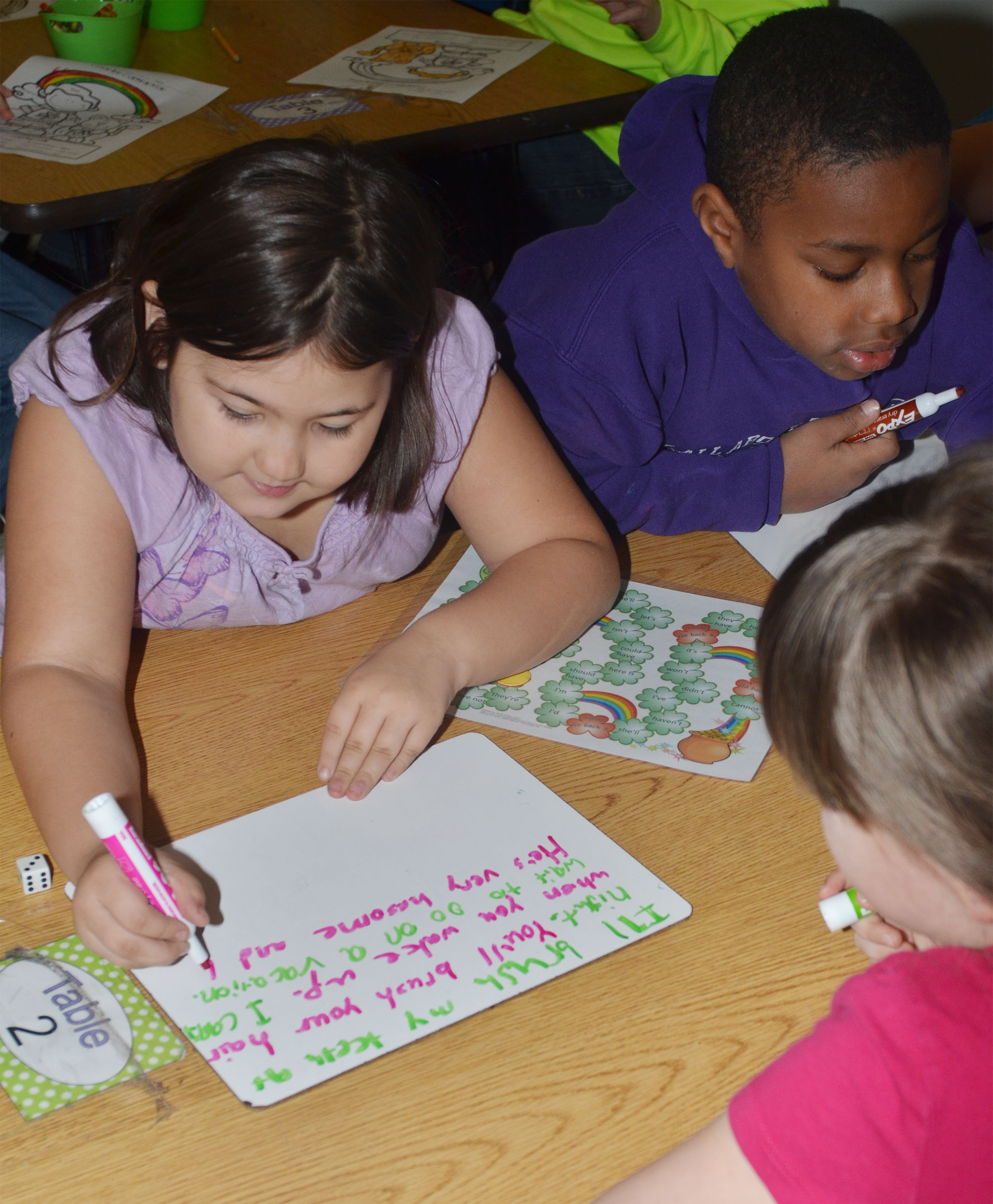 CES second-grader Marissa Sumners writes a sentence using the contractions she landed on while playing the pot of gold game.