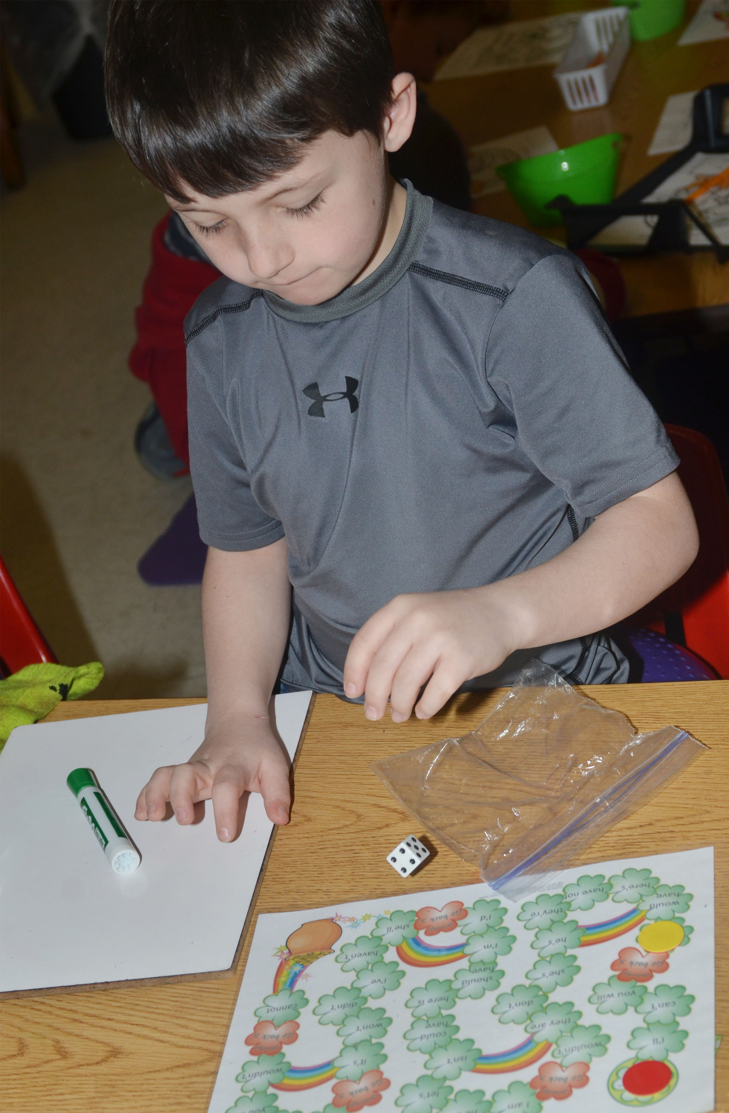 CES second-grader Codey Parks rolls the dice while playing a pot of gold game.