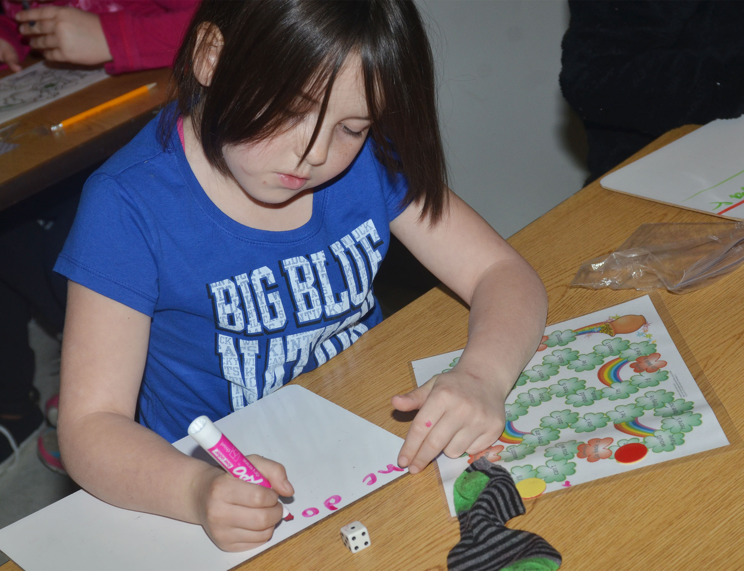 CES second-grader Kendall Cruz writes a sentence using the contraction she landed on while playing the pot of gold game.