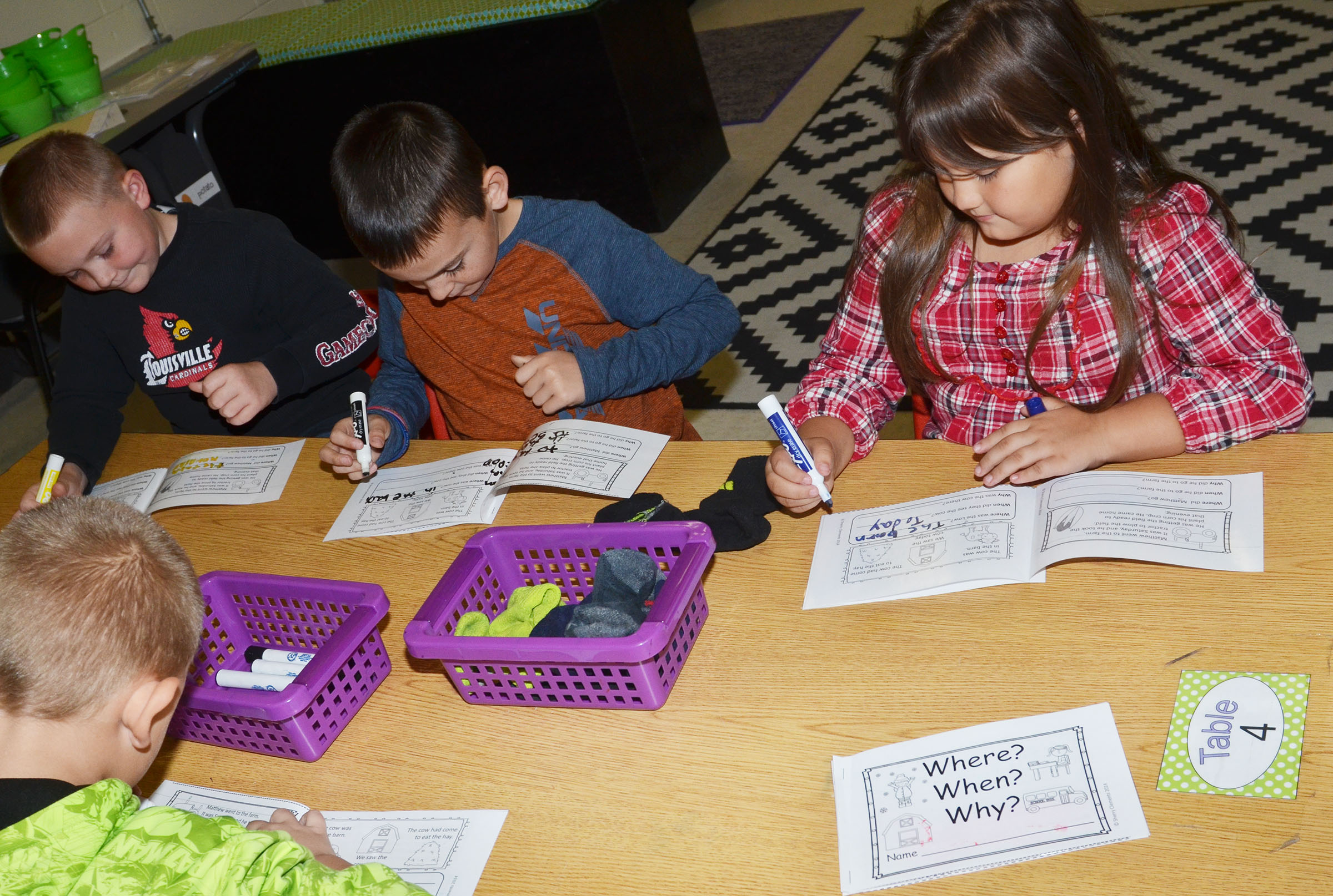 CES second-graders, from left, Griffin Skaggs, Hunter Garmon and Marissa Sumners complete their story element booklets.
