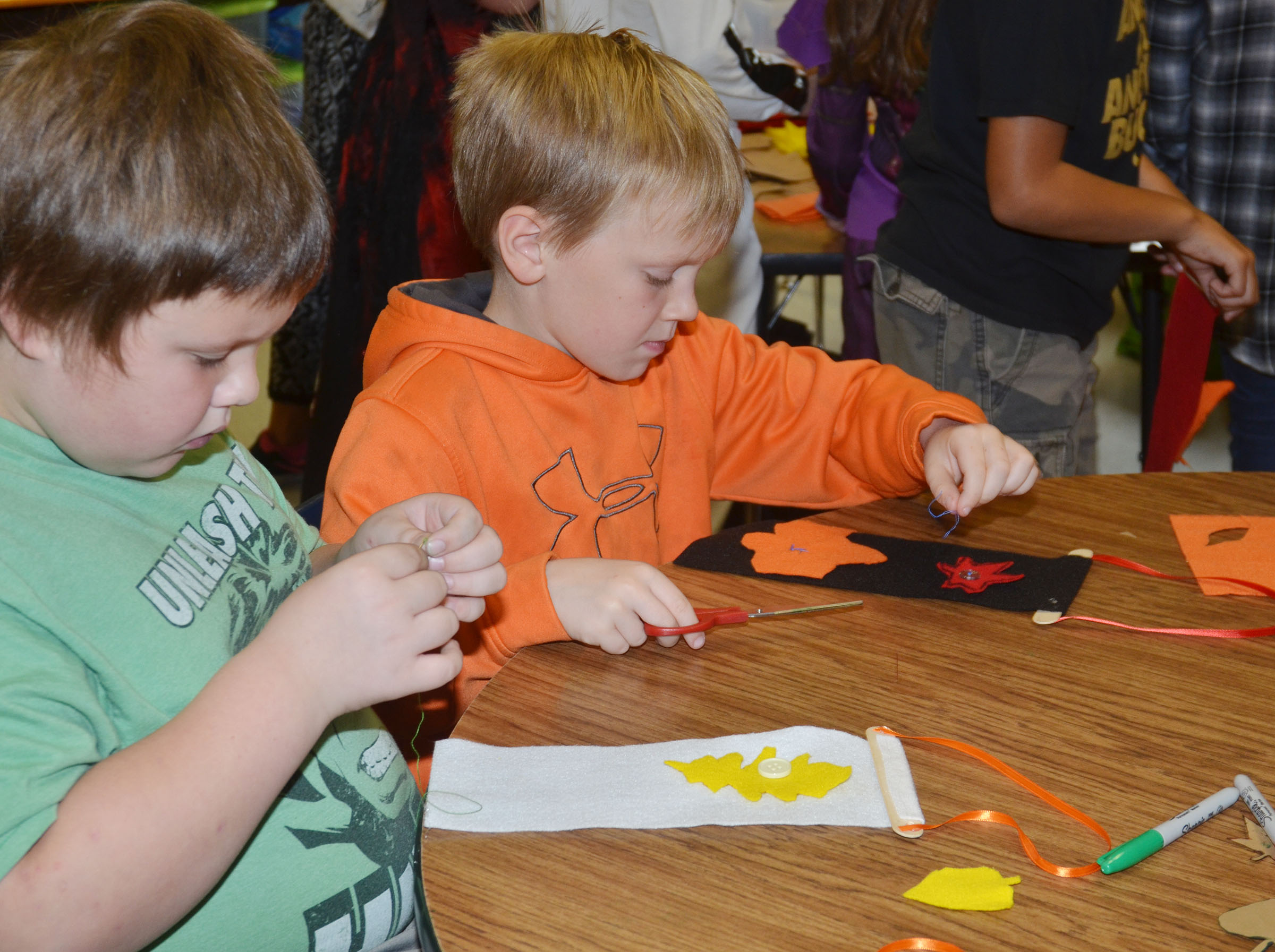 CES third-graders Jace Cox, at left, and Timothy Coots make their door hangers.