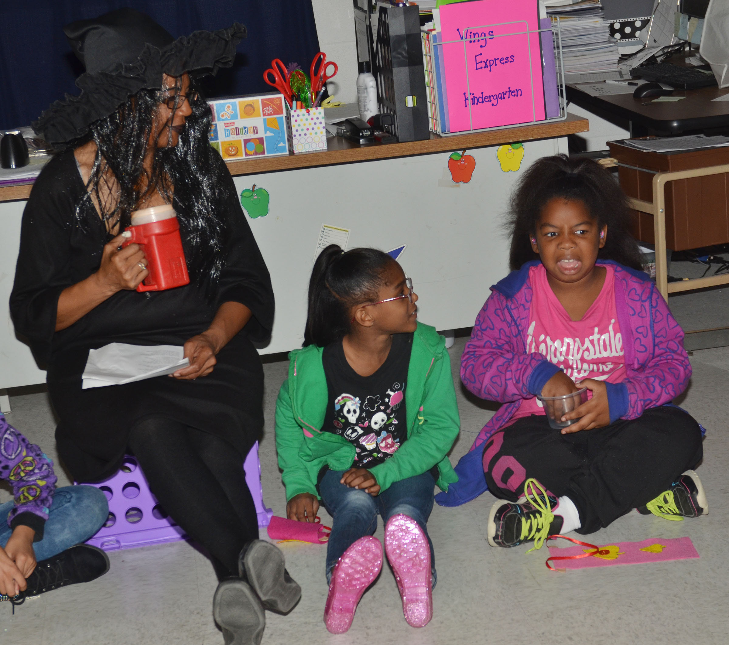 CES third-grade teacher Doretha Sanders, at left, tells a spooky story as students Maliyah Harris, center, and KaMiya Williams feel objects in the dark.