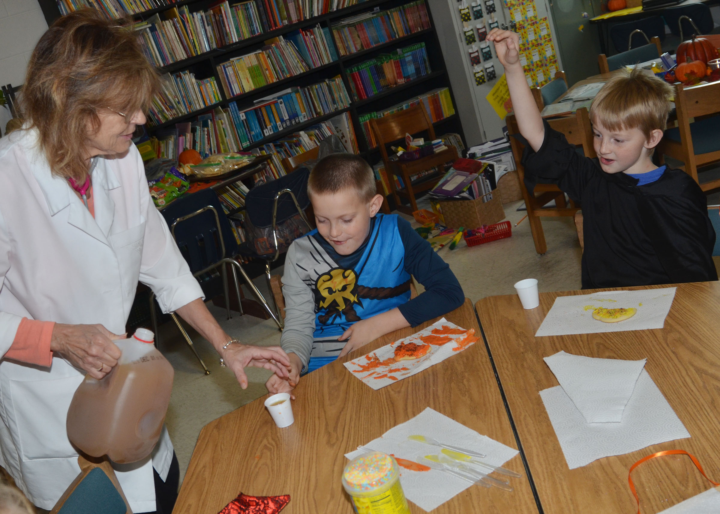 CES third-grade teacher Marcia Sharp serves apple cider as students Bobby Engle, center, and Devin Underwood enjoy the cookies they decorated.