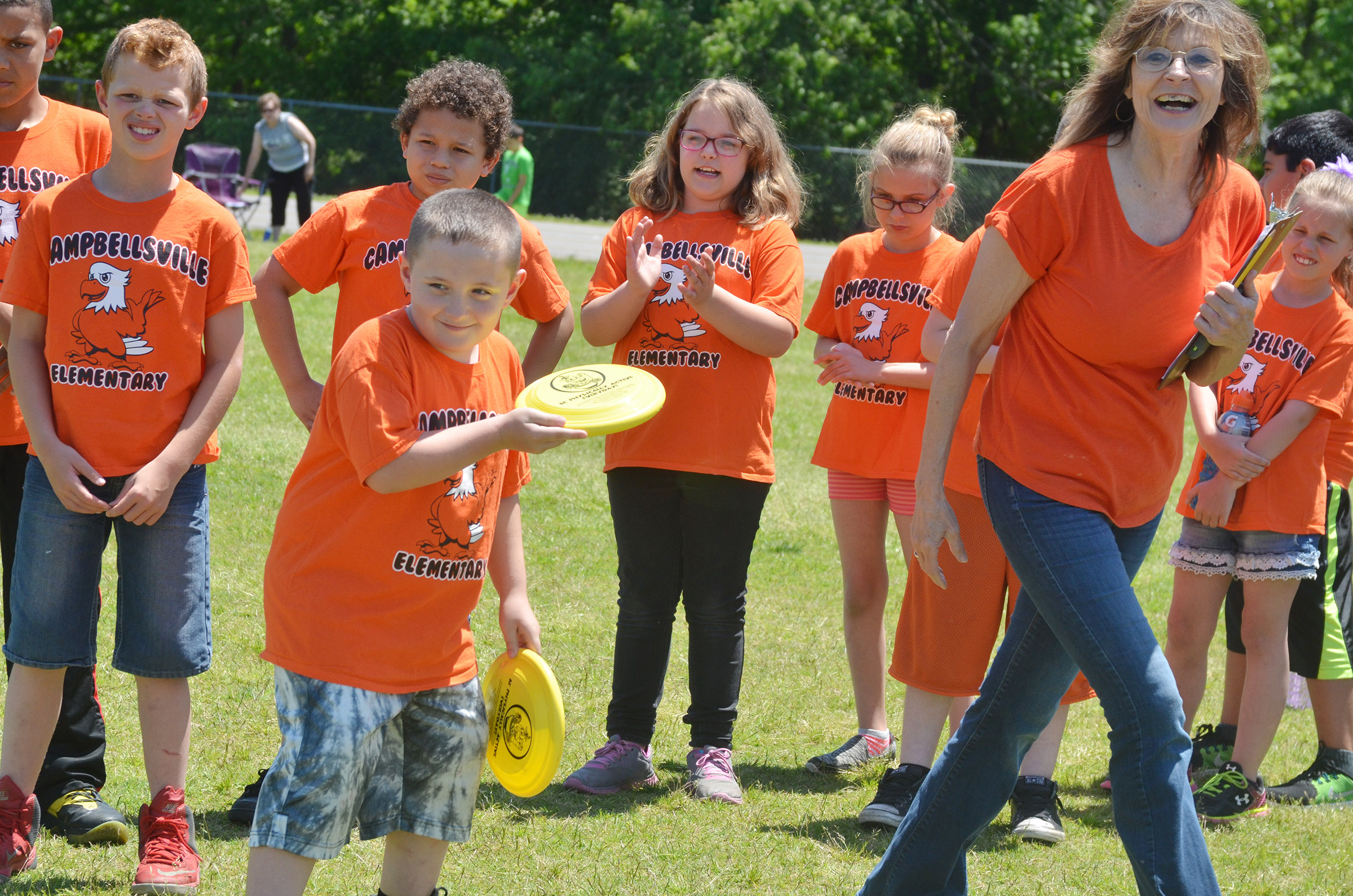 CES third-grade teacher Marcia Sharp cheers for Isaiah Scharbrough as he throws a Frisbee.
