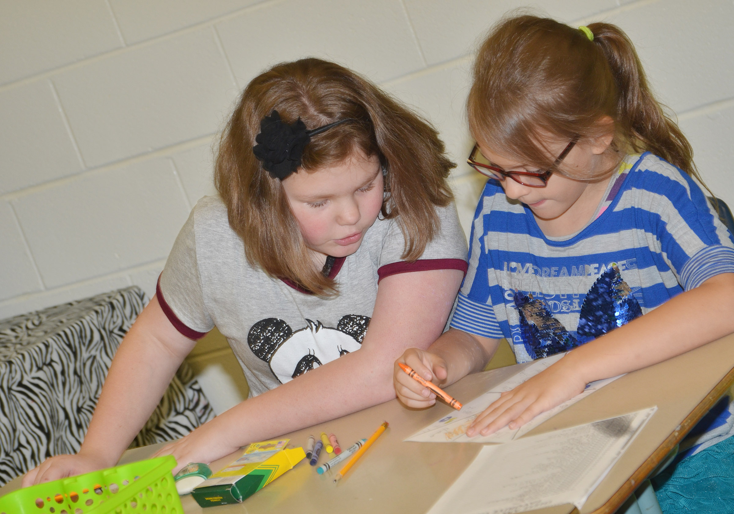 CES fifth-graders Averi Perkins, at left, and Brooklynn Giles complete an assignment to help their teacher learn about them.