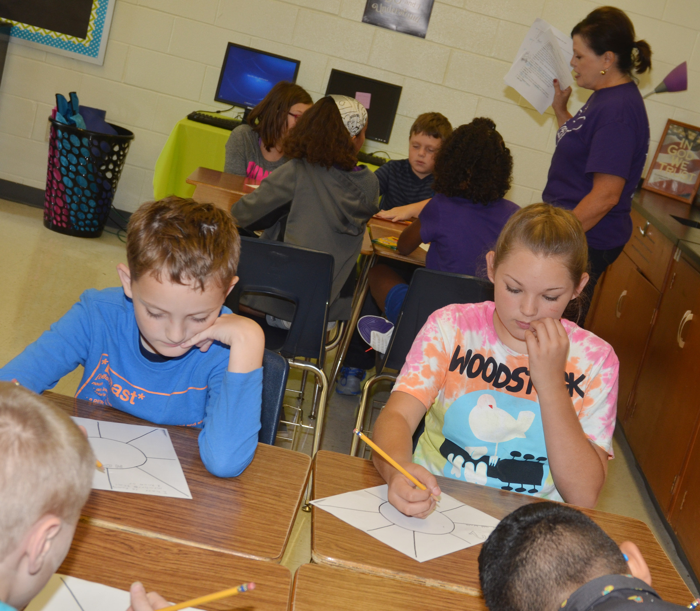 CES fifth-graders Noah Leachman, at left, and Piper Maggard complete a worksheet to help their teacher, Lisa Kearney, in the background, learn about them.