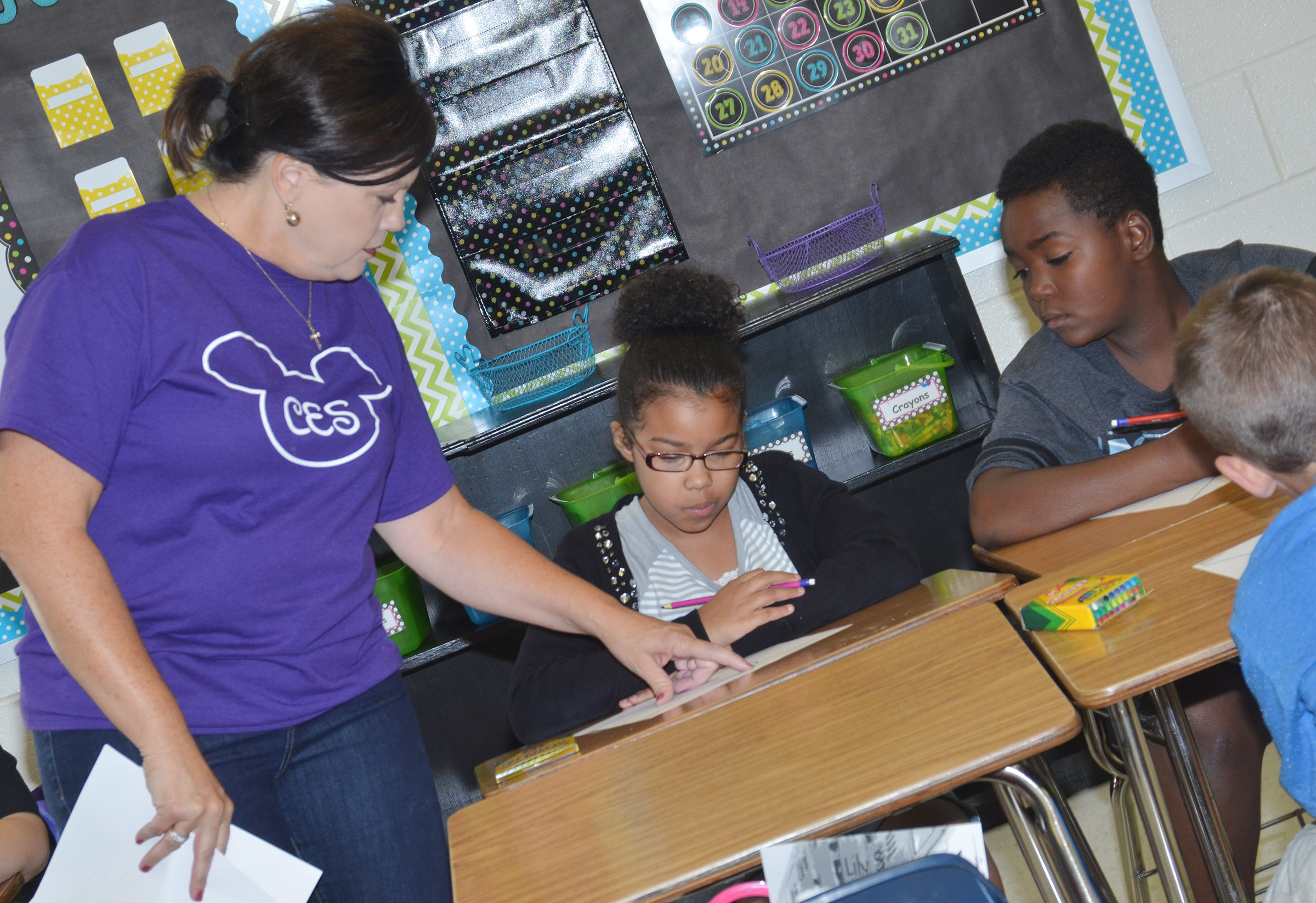 CES fifth-grade teacher Lisa Kearney helps Serenity Mings and Deason Smith with an assignment.