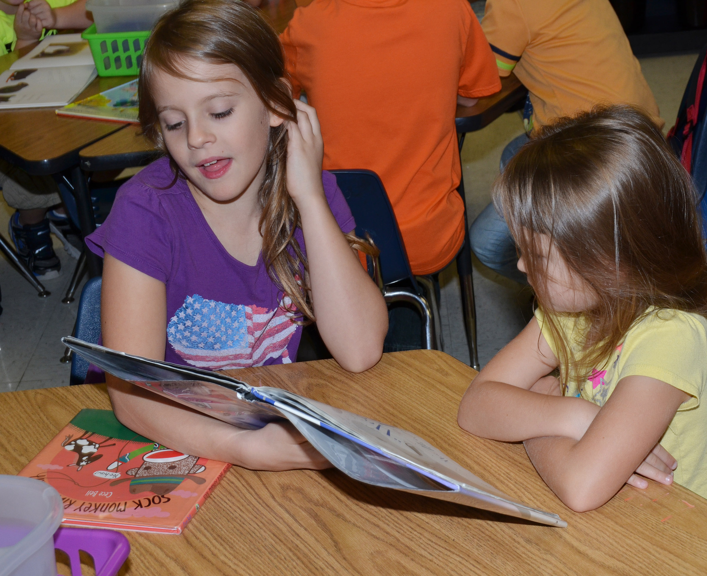 CES fifth-grader Ellie Wise reads to kindergartener Lillie Spencer.