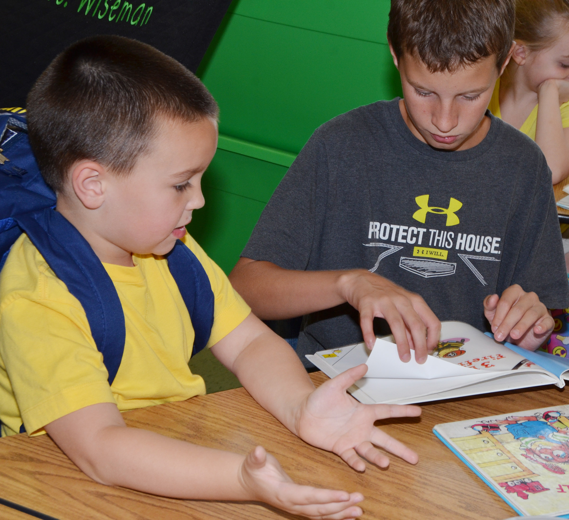 CES fifth-grader Rowan Petett reads to kindergartener Xander Britton.