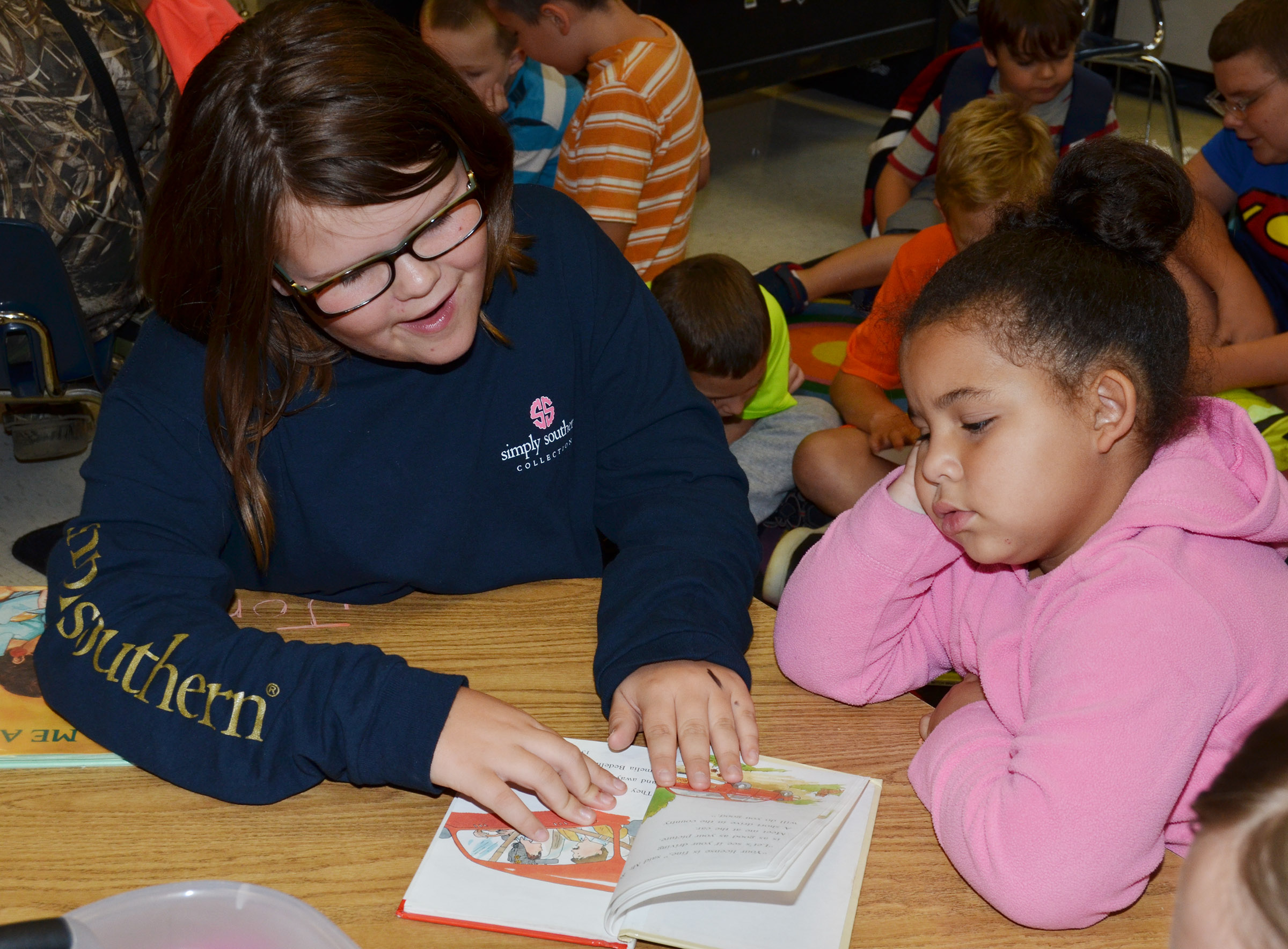 CES fifth-grader Keeley Dicken reads to kindergartener Tatum Hoskins.