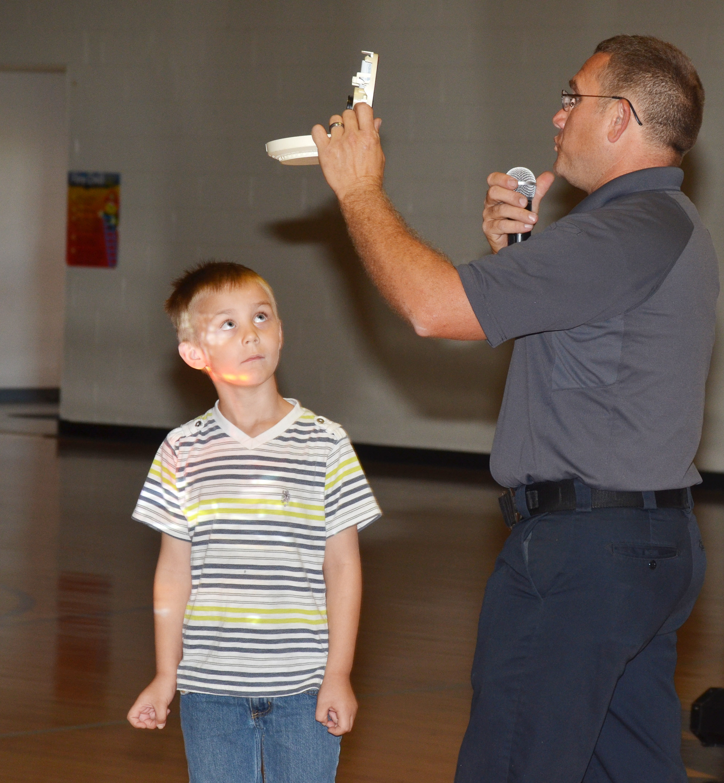 Campbellsville Fire & Rescue Captain Keith Bricken talks to CES second-grader Hunter Bates about the proper way to check the battery in a smoke detector.
