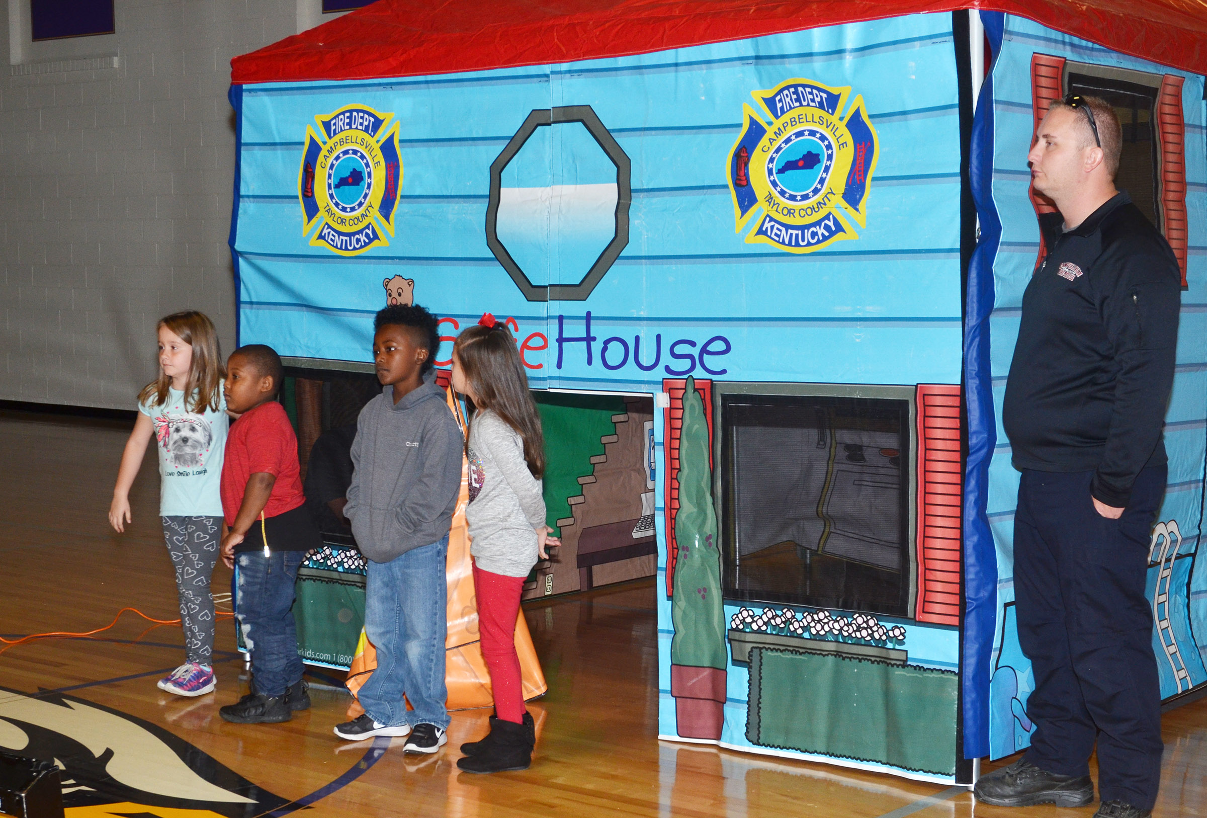 Campbellsville Fire & Rescue Firefighter Daniel Cook helps CES students, from left, first-graders Natalee Shaw and Malachi Conner and second-graders Drelynn Hollins and Lillian Martin know the proper way to leave a home when a smoke detector sounds.