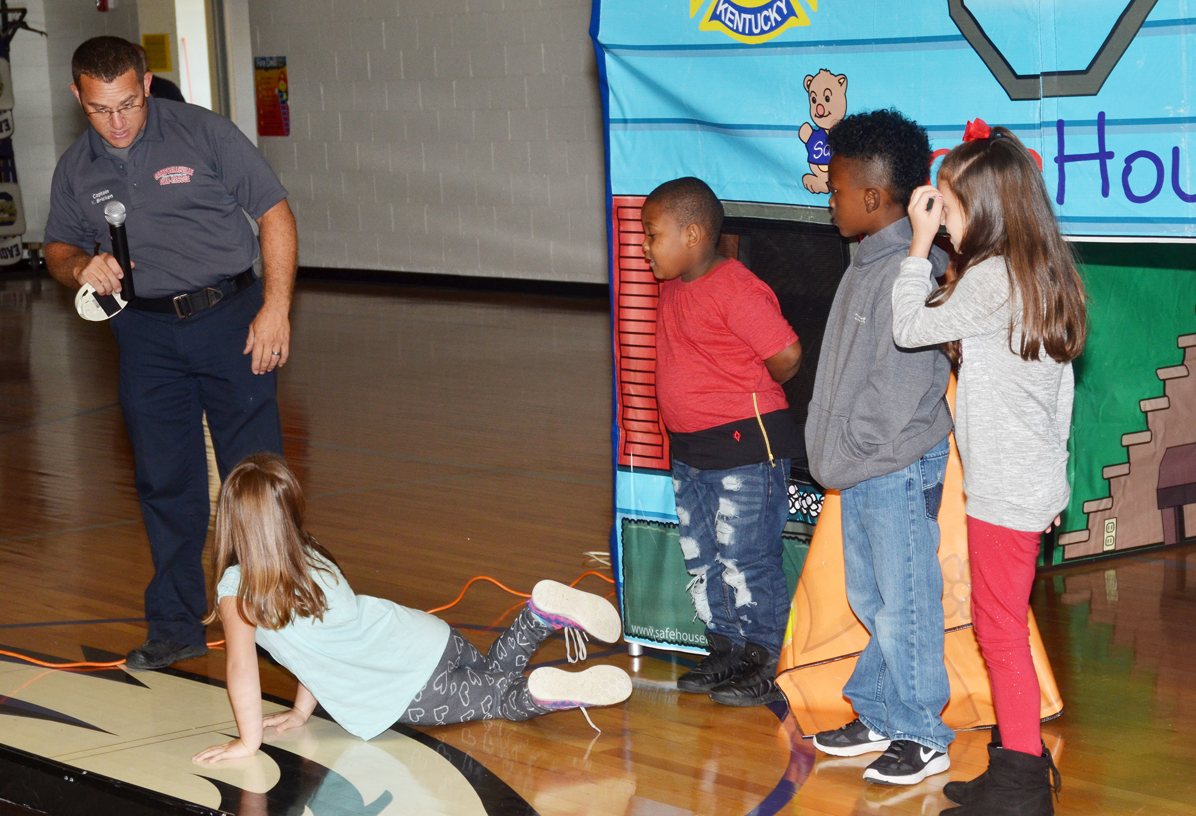 Campbellsville Fire & Rescue Captain Keith Bricken helps CES students, from left, first-graders Natalee Shaw and Malachi Conner and second-graders Drelynn Hollins and Lillian Martin learn the proper way to leave a home when a smoke detector sounds.