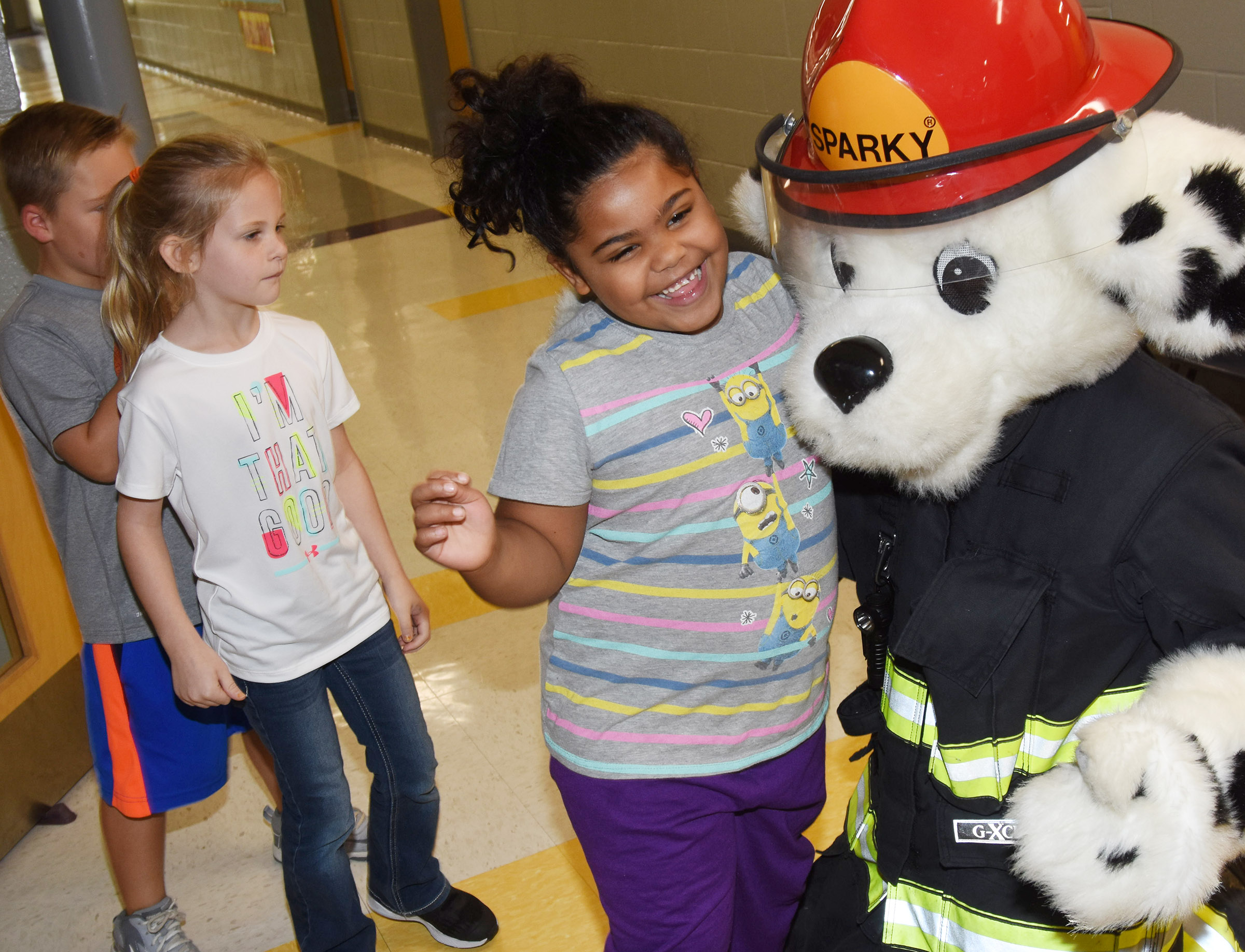 Sparky the fire dog hugs CES first-grader Linnly Adams.