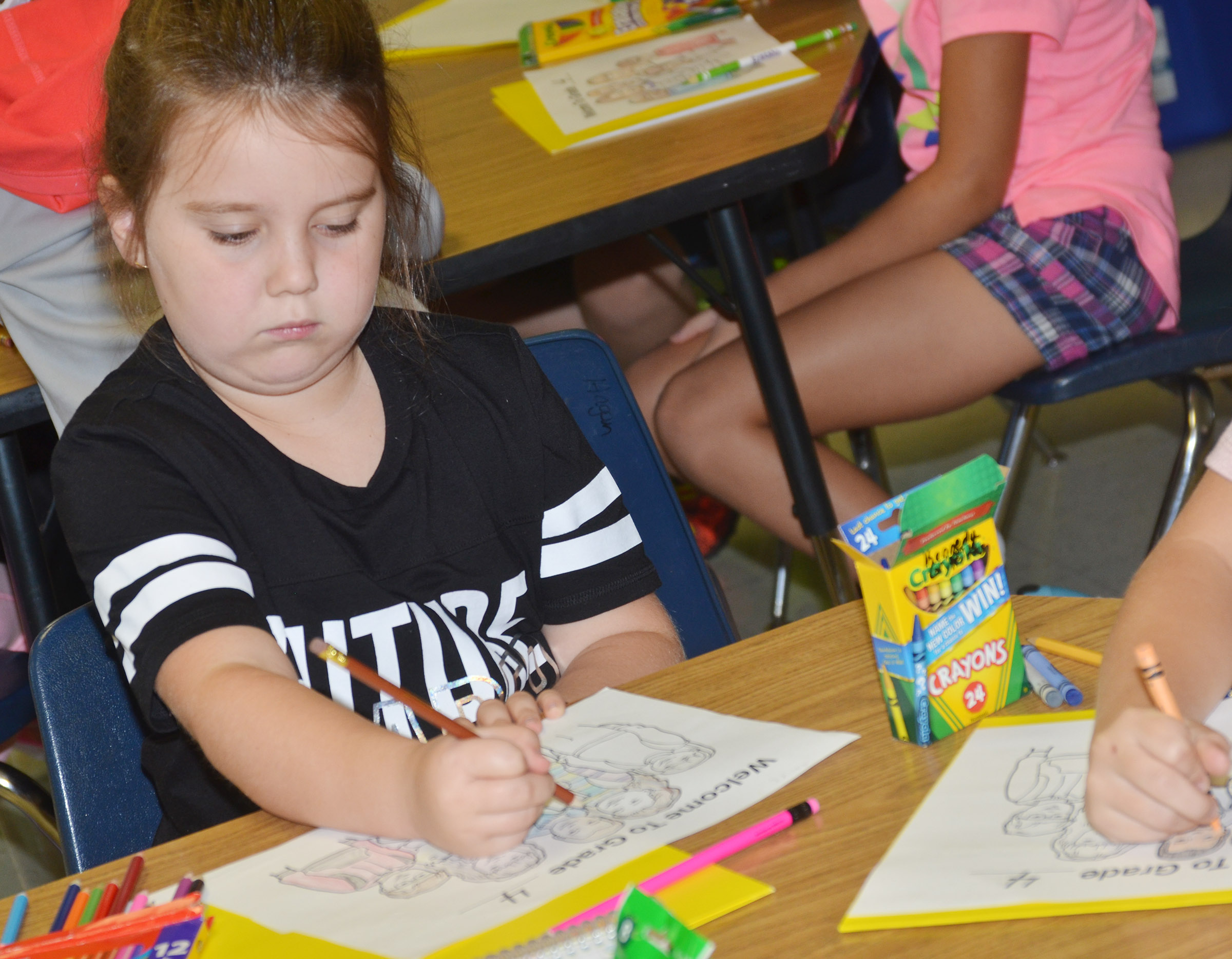 Maylee Wilds colors a picture on her first day of fourth grade at CES.