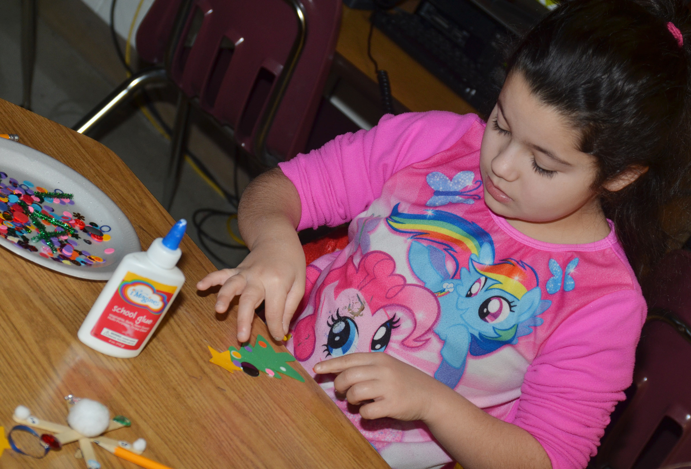 CES third-grader Brooklyn Boudreaux makes a Christmas tree ornament.